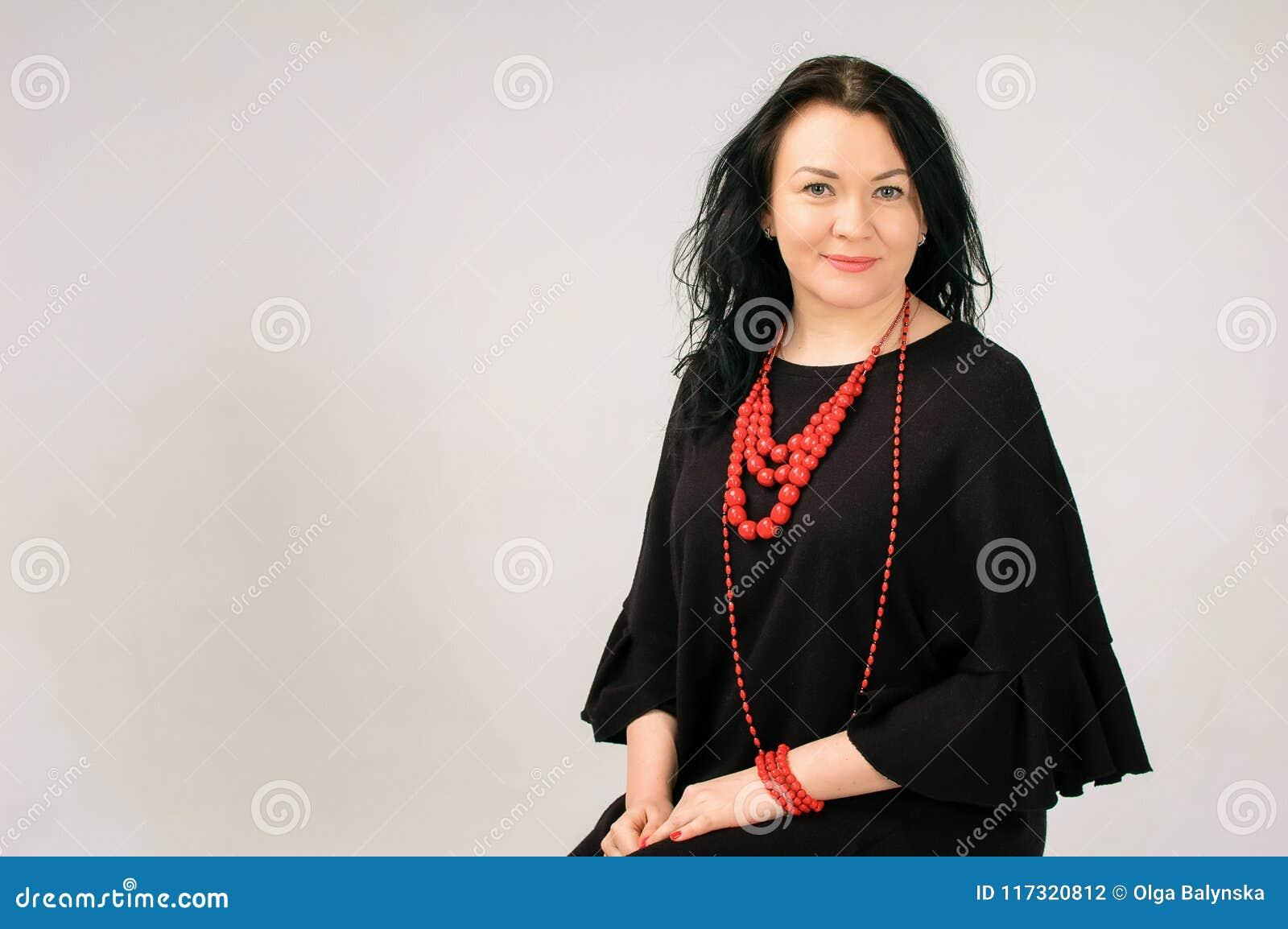Full figurerad kvinna i svart klänning och rött etniskt halsbandsammanträde på stolen i studion, kopieringsutrymme på vänstra sid