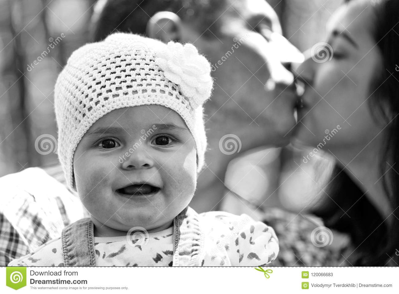 32244a6322a Girl cute smiling baby hazel-eyed kid tiny little child wearing white  flower beanie hat in arms of kissing parents mother and father family  summer day on ...