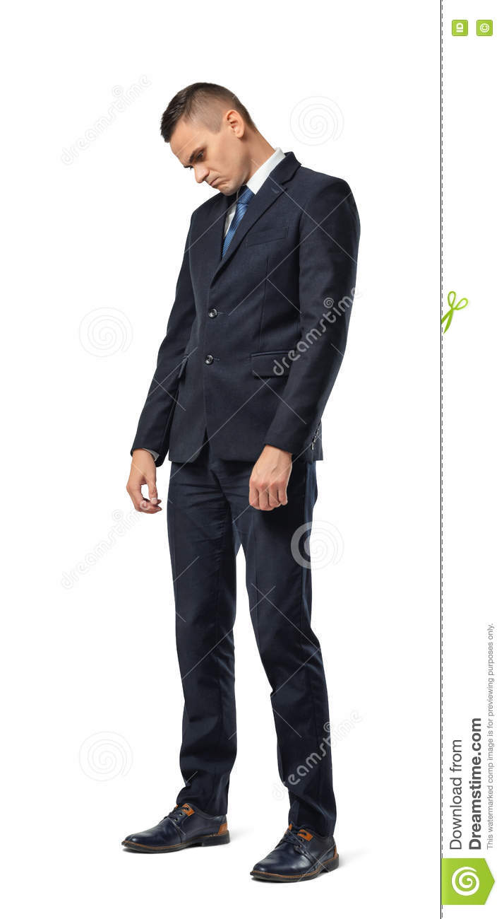 Full growth portrait of businessman standing with bowed head and looking sad isolated on white background