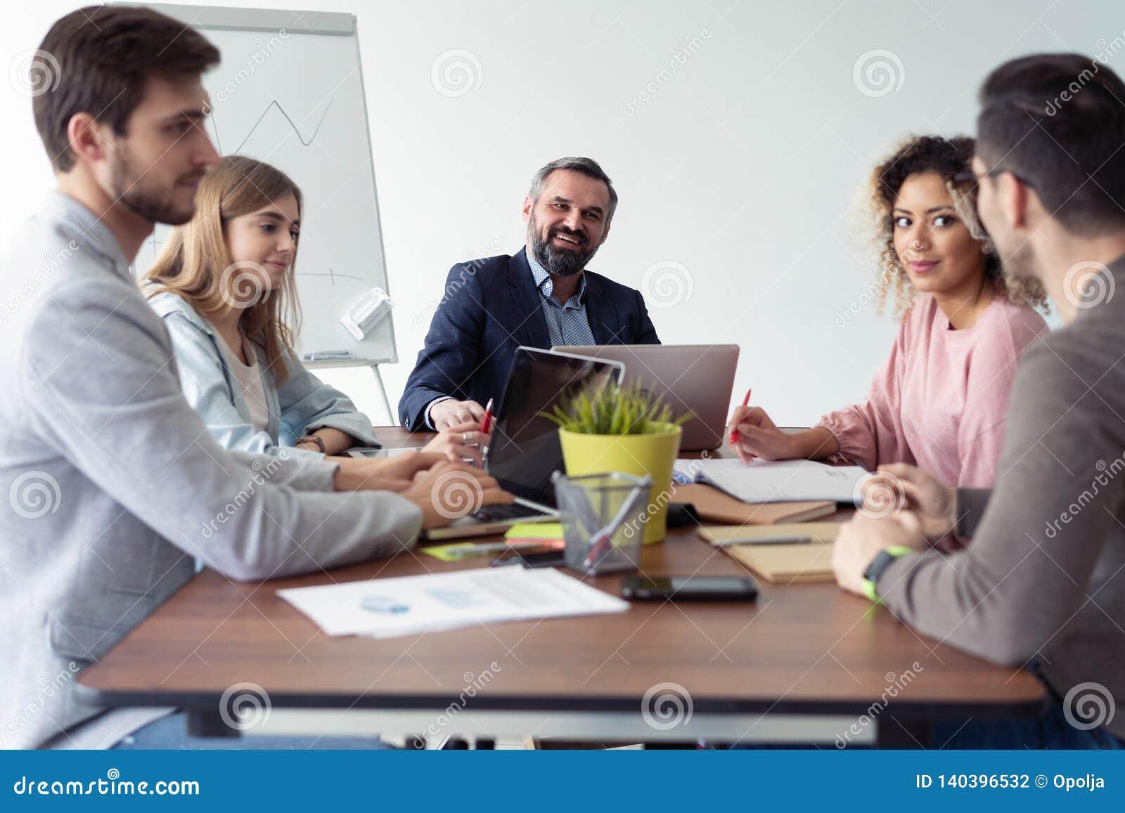 Full koncentration på arbete Grupp av ungt affärsfolk som arbetar och meddelar, medan sitta på kontorsskrivbordet