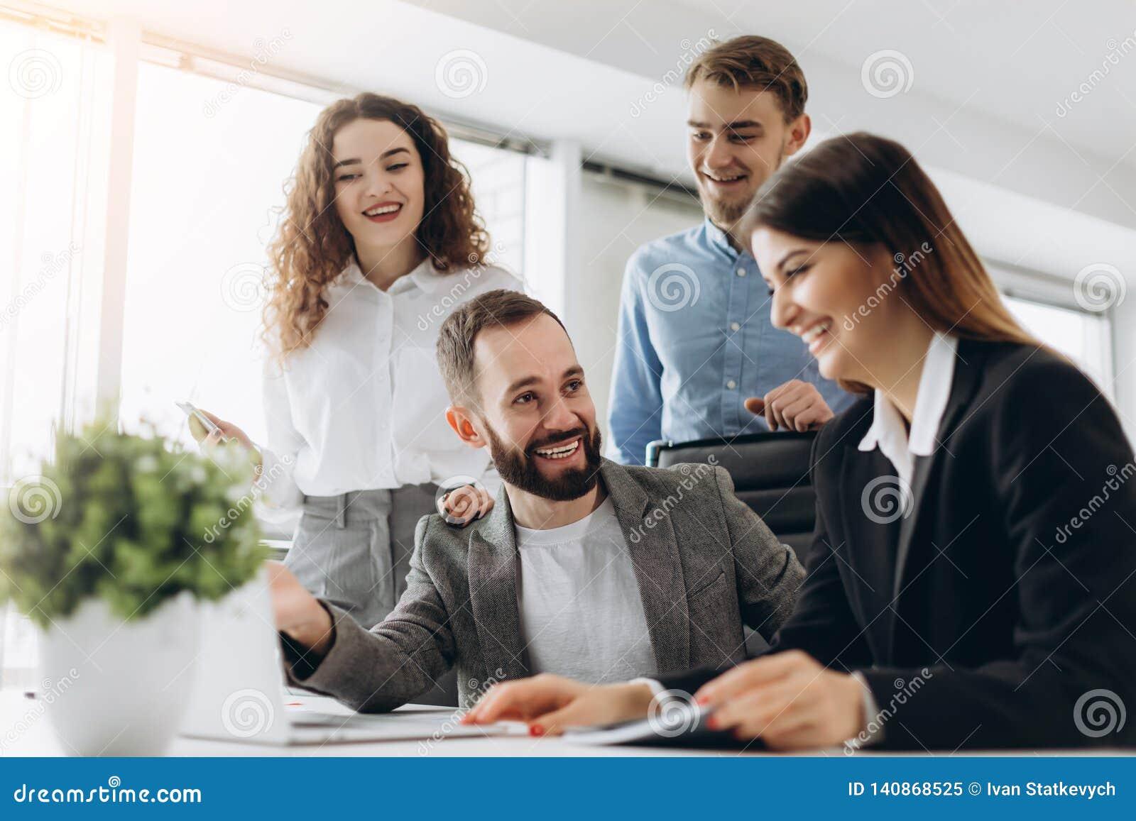 Full koncentration på arbete Grupp av ungt affärsfolk som arbetar och meddelar, medan sitta på kontorsskrivbordet tillsammans