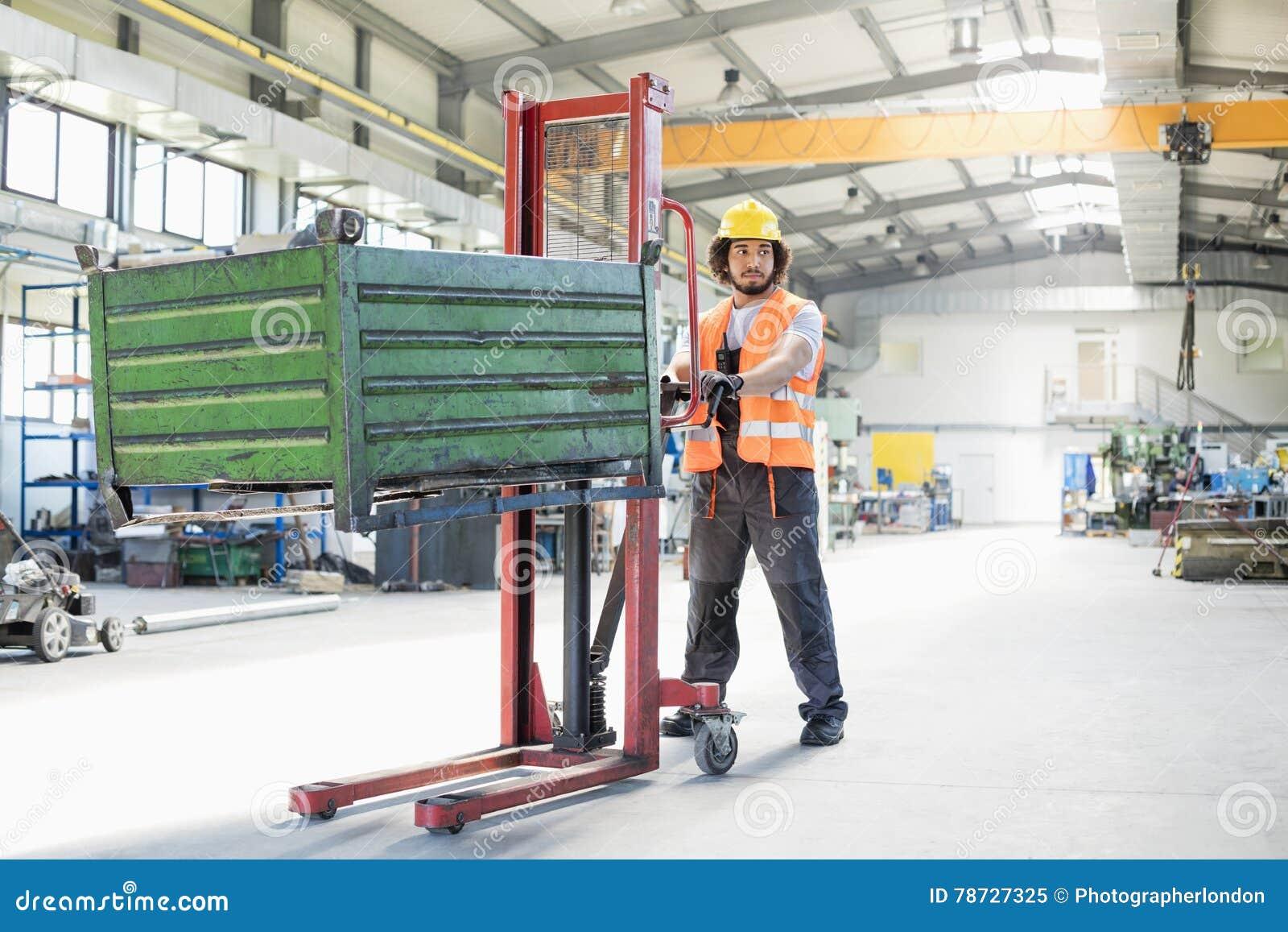Full längd av den unga driftiga handlastbilen för manuell arbetare med heavy metal i bransch