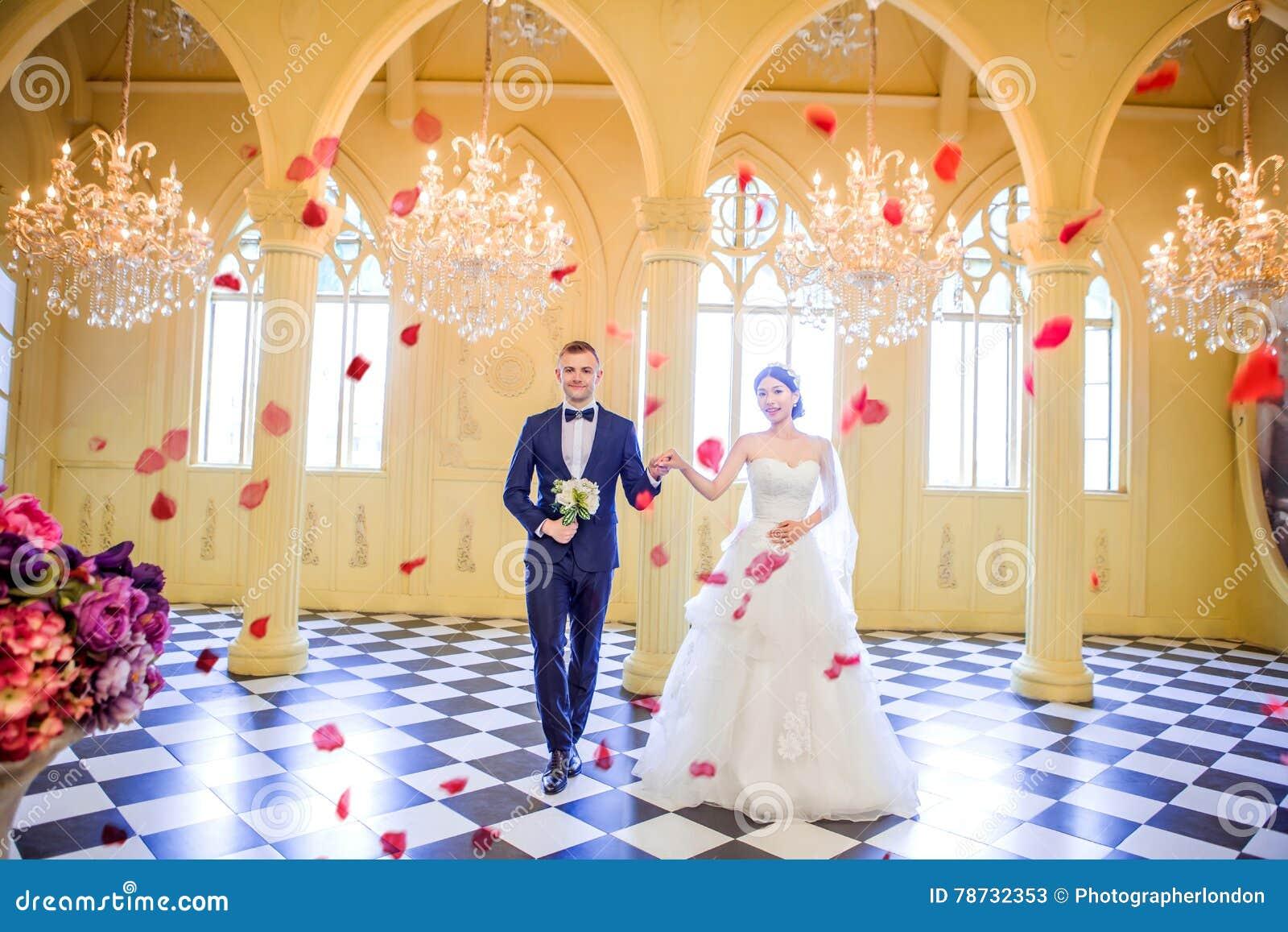 Full längd av eleganta händer för bröllopparinnehav i kyrka