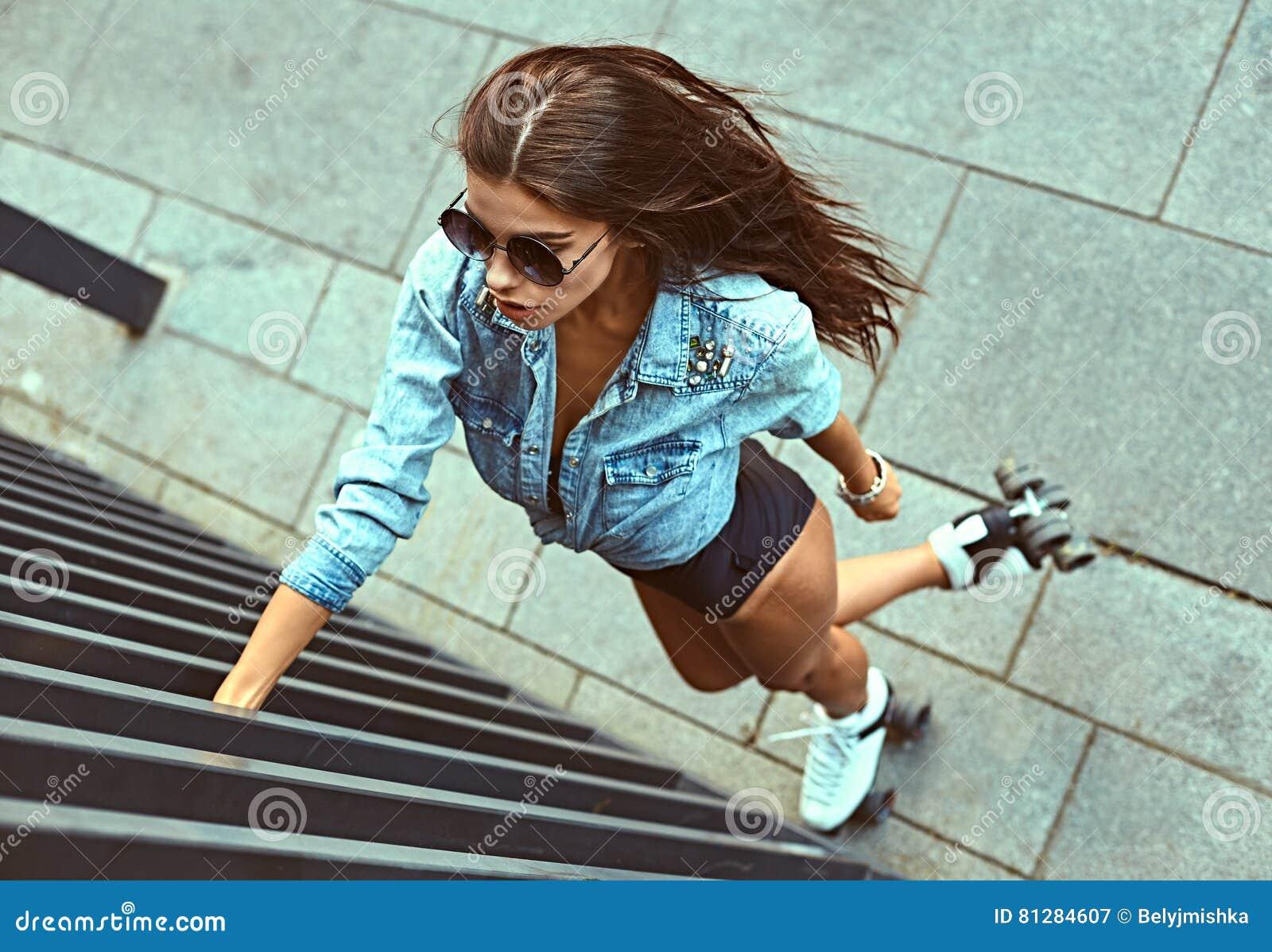 Full längd av lyckligt åka skridskor för rulle för ung kvinna