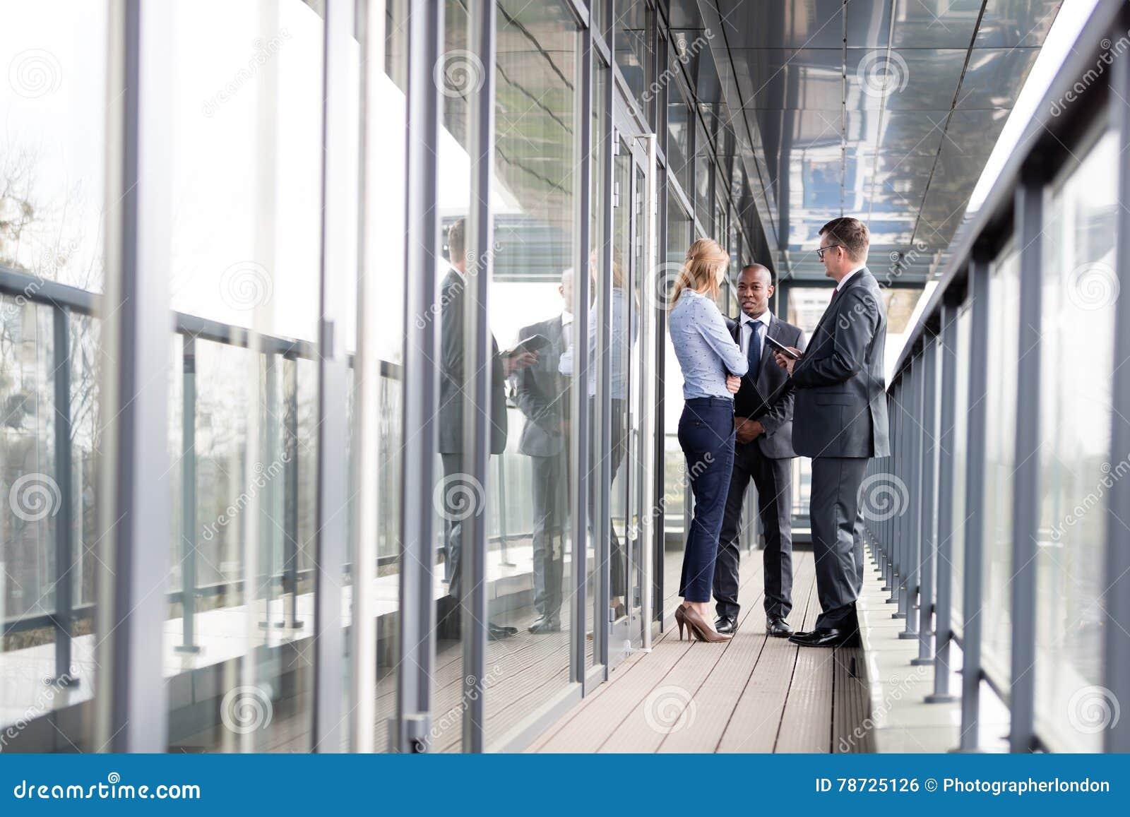 Full längd av mång--person som tillhör en etnisk minoritet affärsfolk som diskuterar på kontorsbalkong