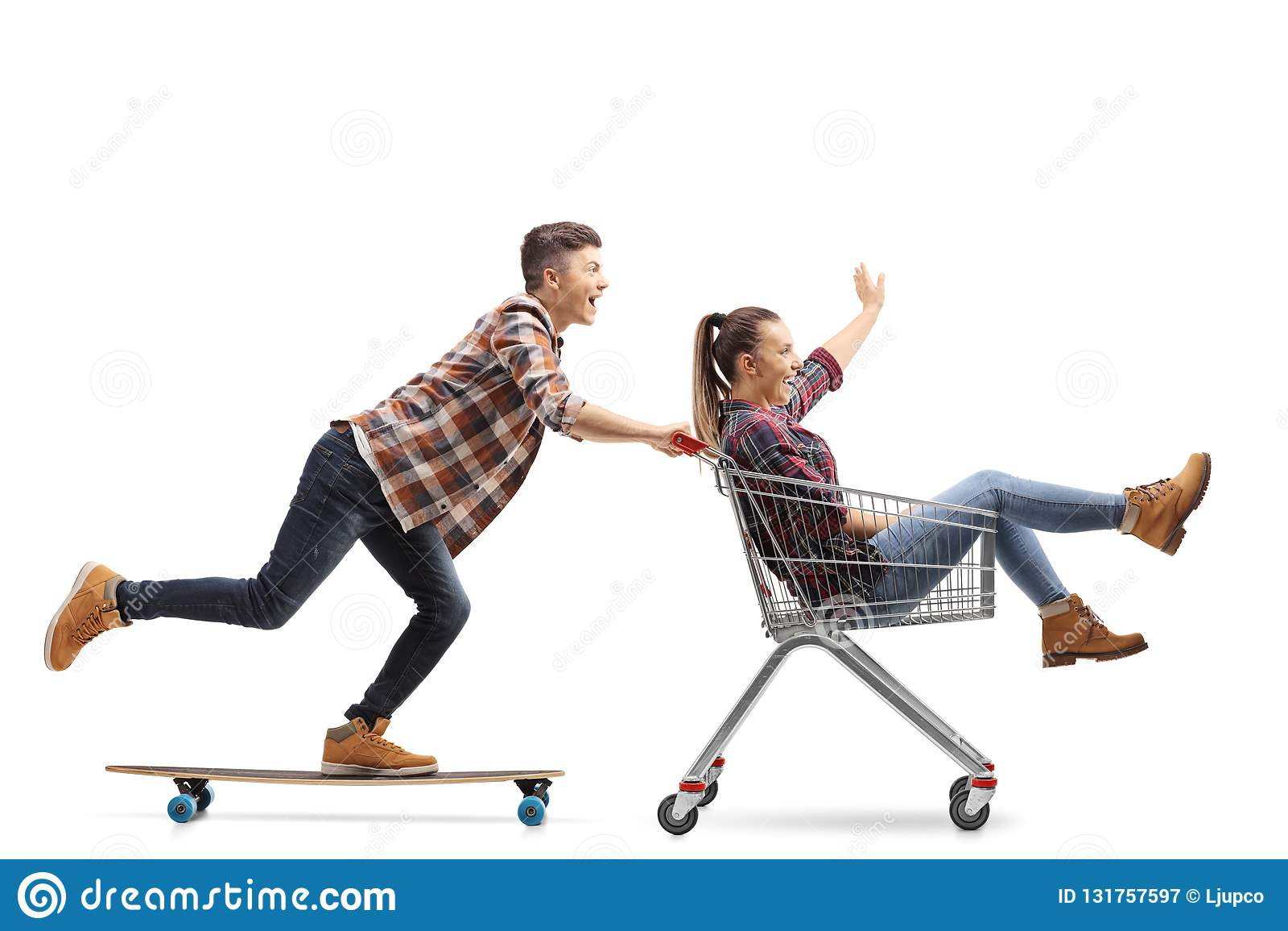 Full längd som skjutas av en ung grabb som rider en longboard och skjuter en flicka i en shoppa vagn som isoleras på vit bakgrund
