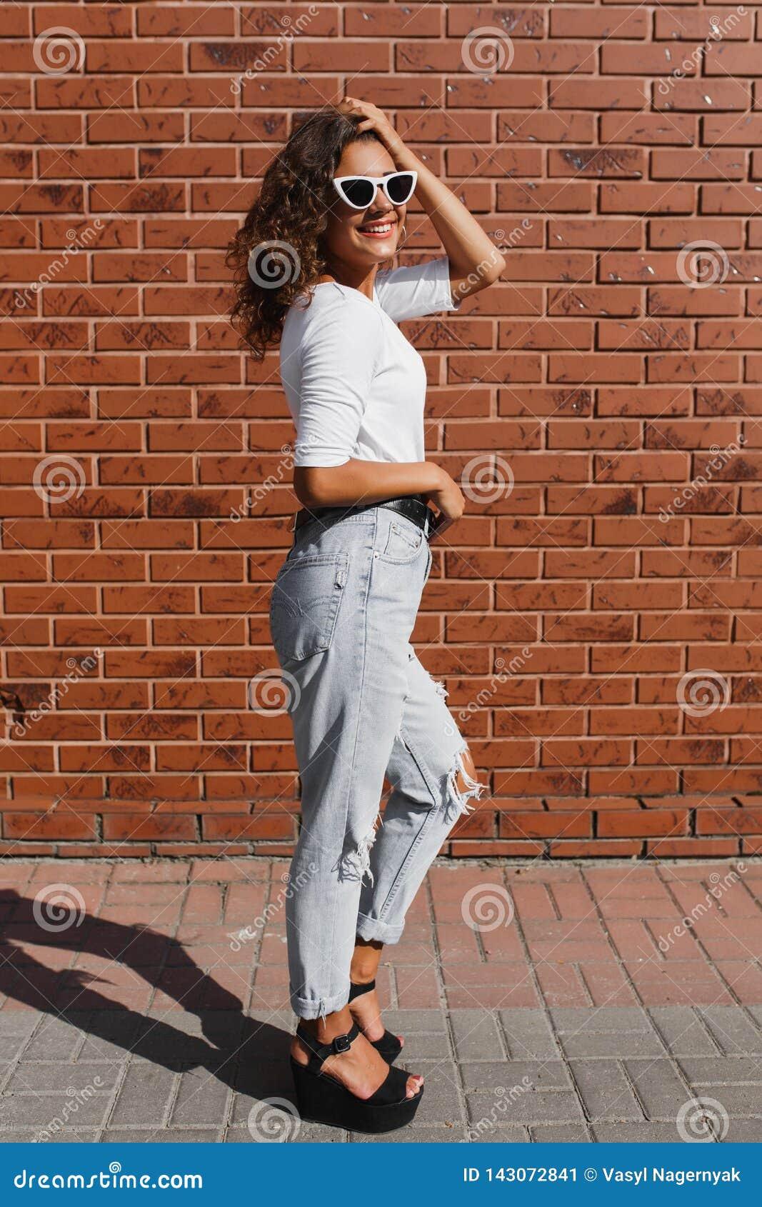 Full längdstående av den härliga gulliga unga kvinnan med långt lockigt hår i den vita t-skjortan
