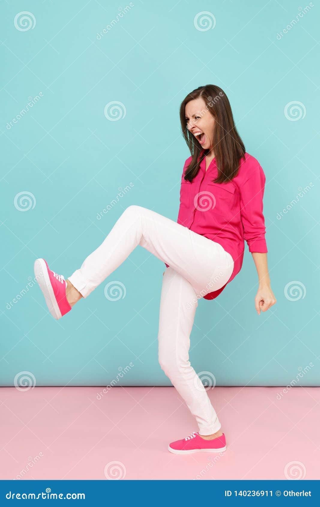 Full längdstående av den ilskna roliga unga nätta kvinnan i den rosa skjortablusen, vitt posera för flåsanden som isoleras på lju