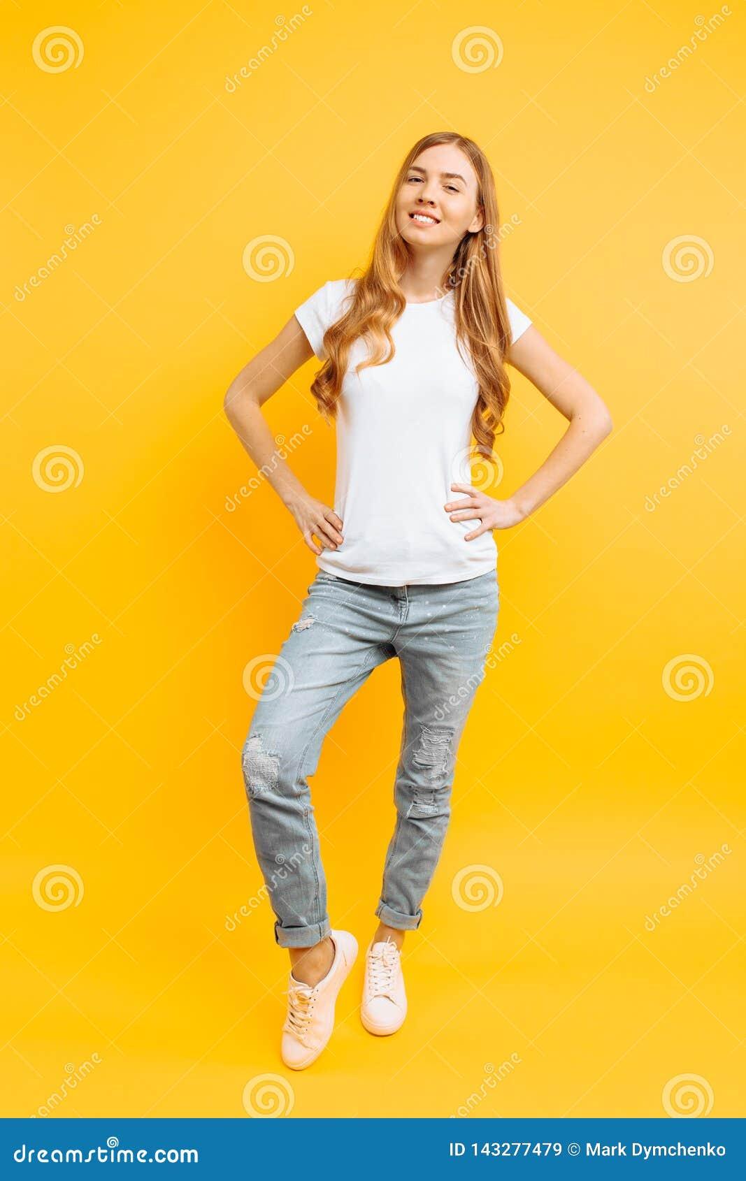 Full längdstående av en gladlynt härlig flicka som poserar på en gul bakgrund