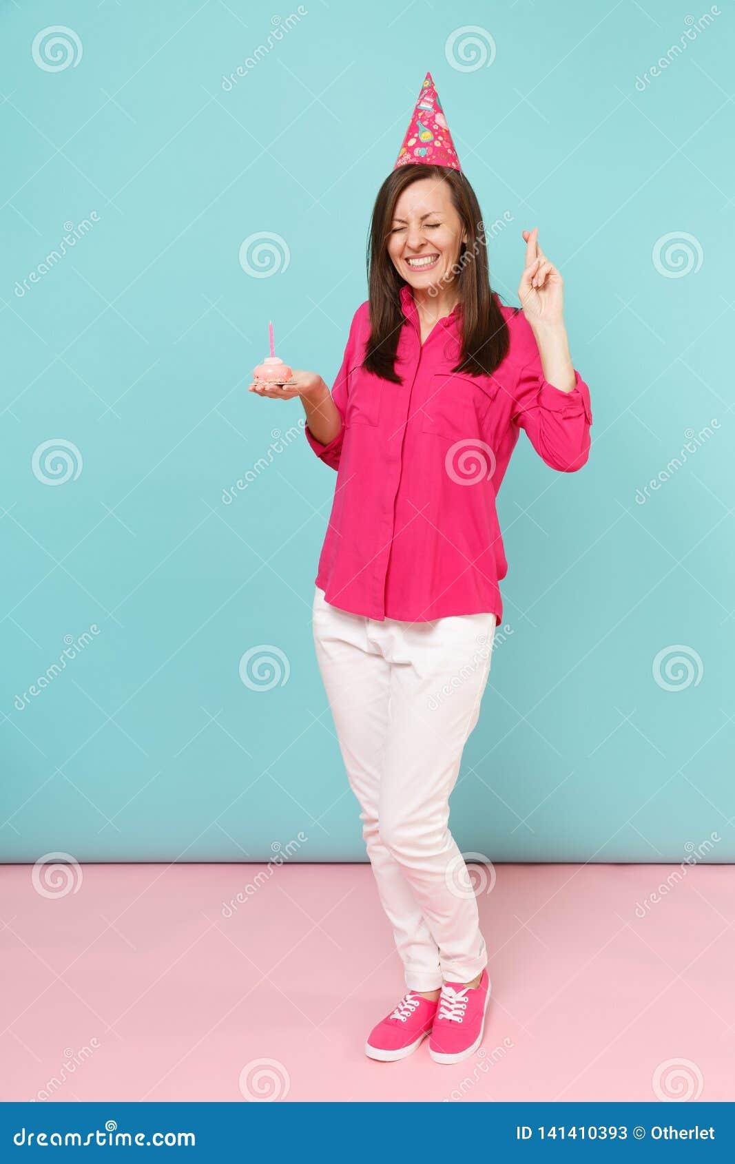 Full längdståendekvinna i den rosa skjortablusen, vita flåsanden, födelsedaghatt med att posera för muffin som isoleras på ljusa