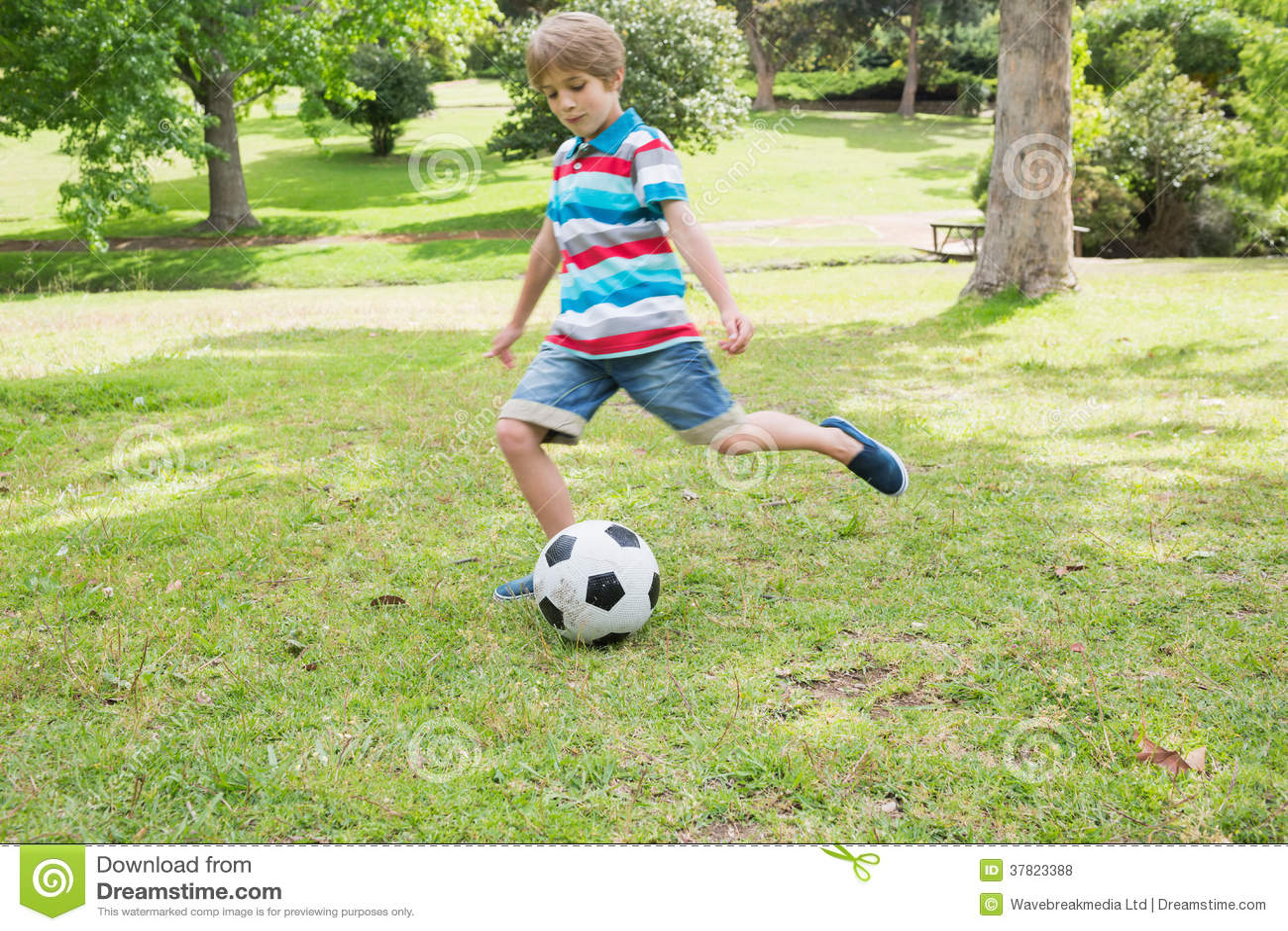 Full length of a boy kicking ball at park