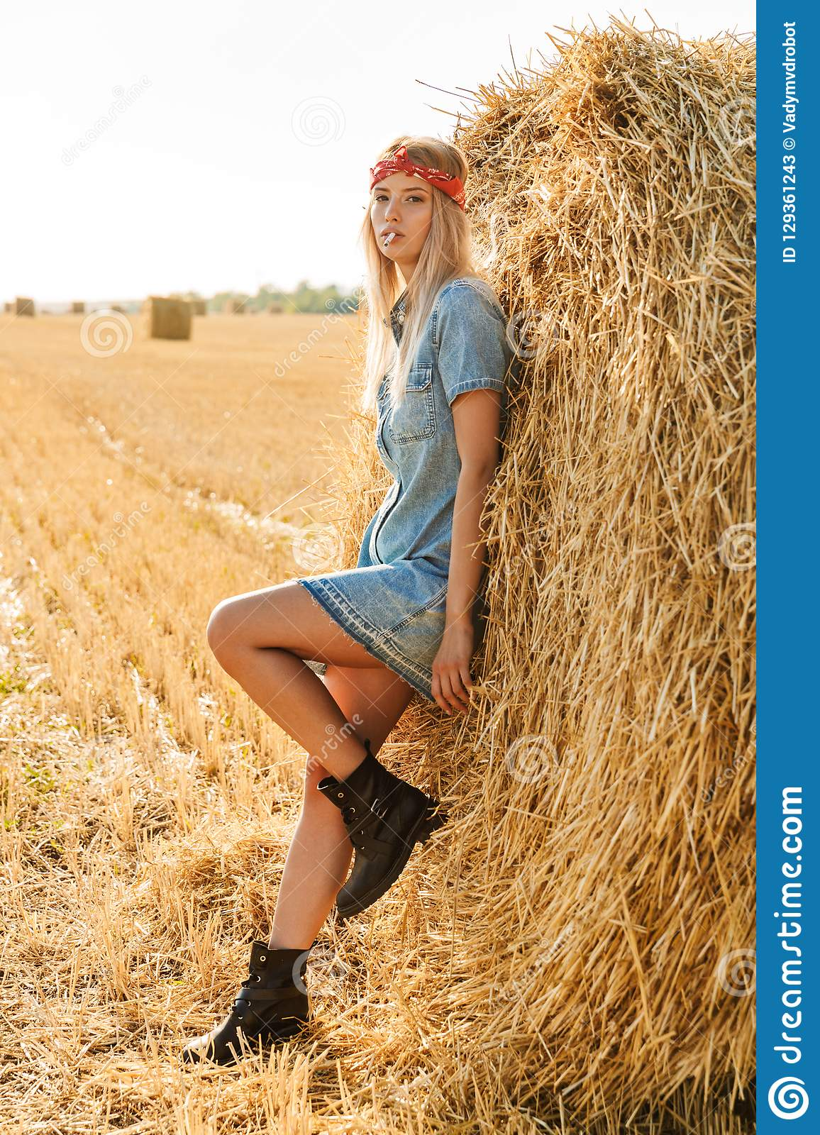 Full length image of gorgeous woman 20s standing near big haystack in golden field, and smoking cigarette during sunny day