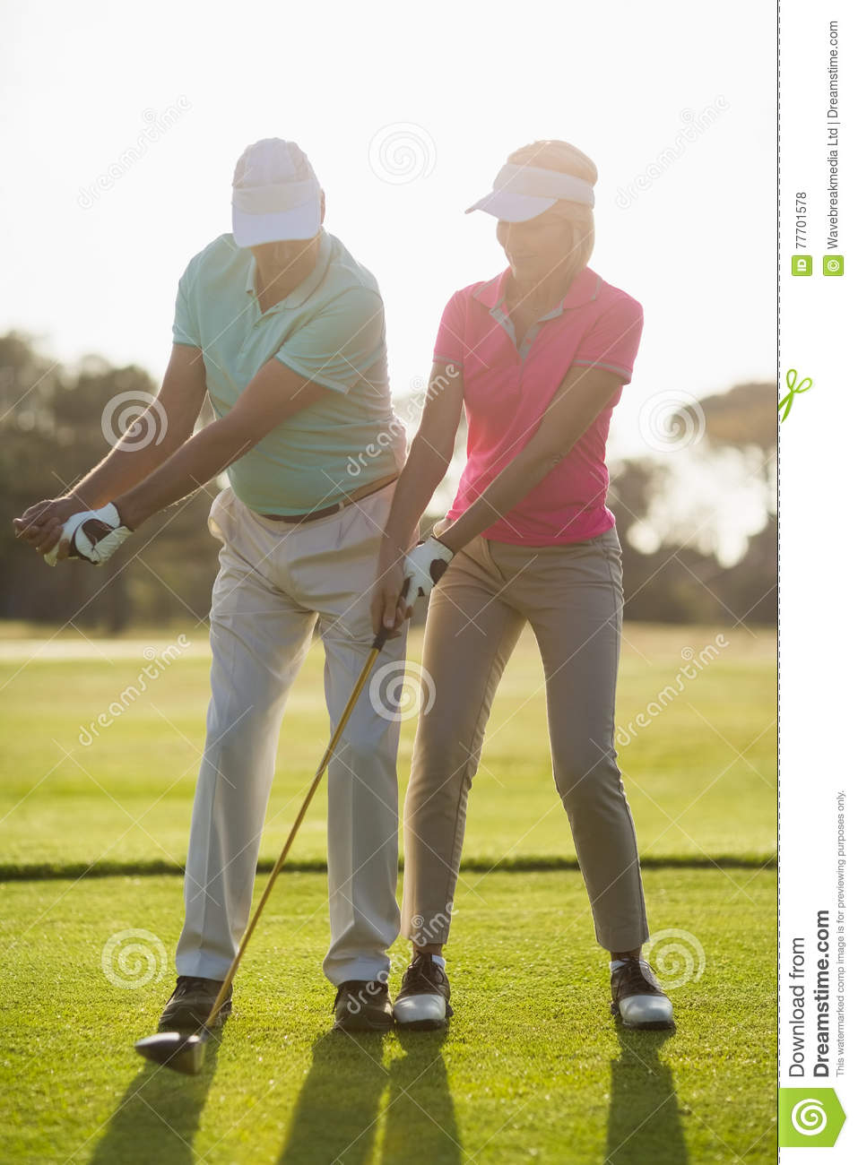 Full length of mature male golf player teaching woman