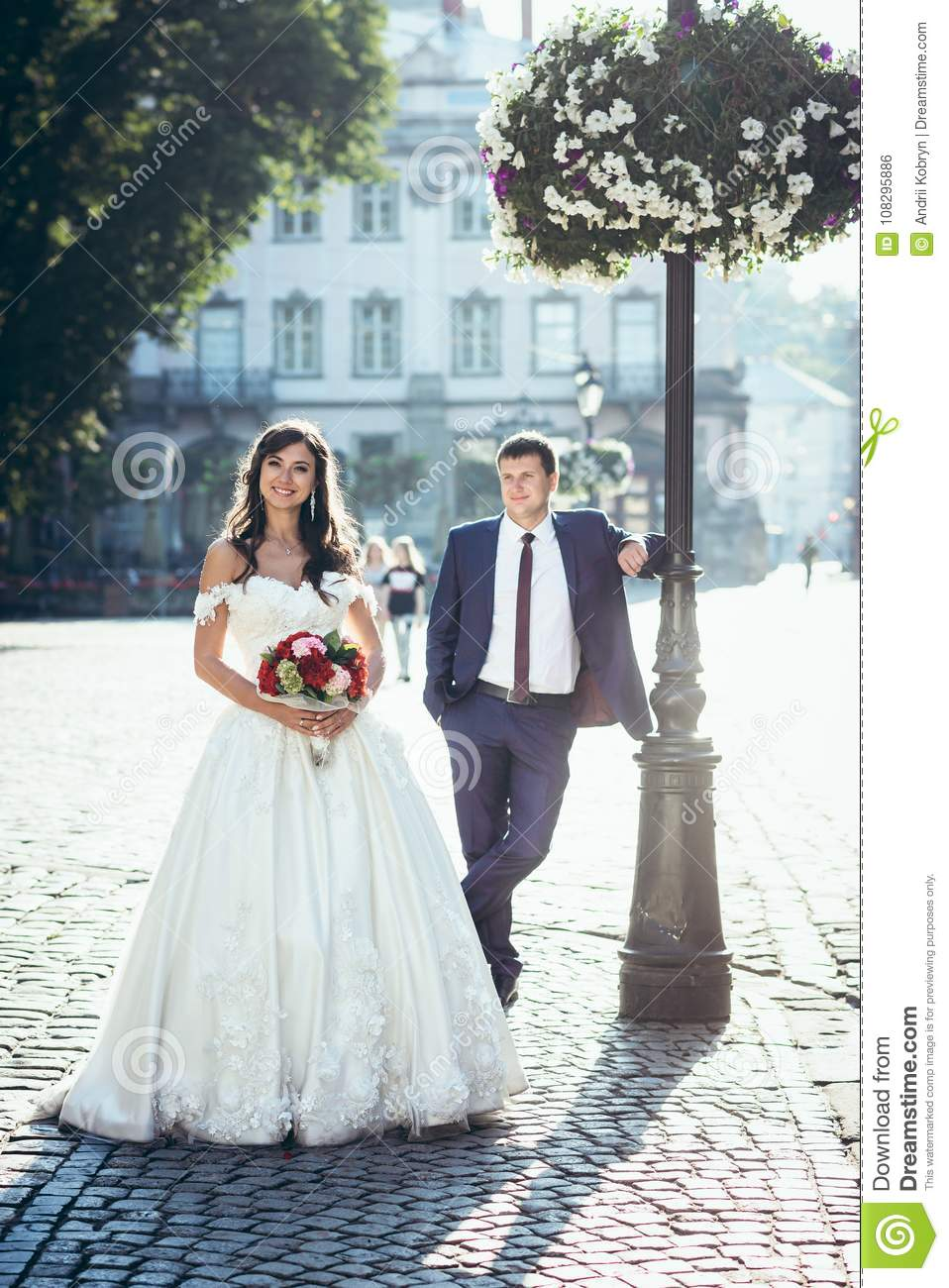 405aa0a55f8 Full-length outdoor wedding portrait. The beautiful brunette bride with the  bouquet of red