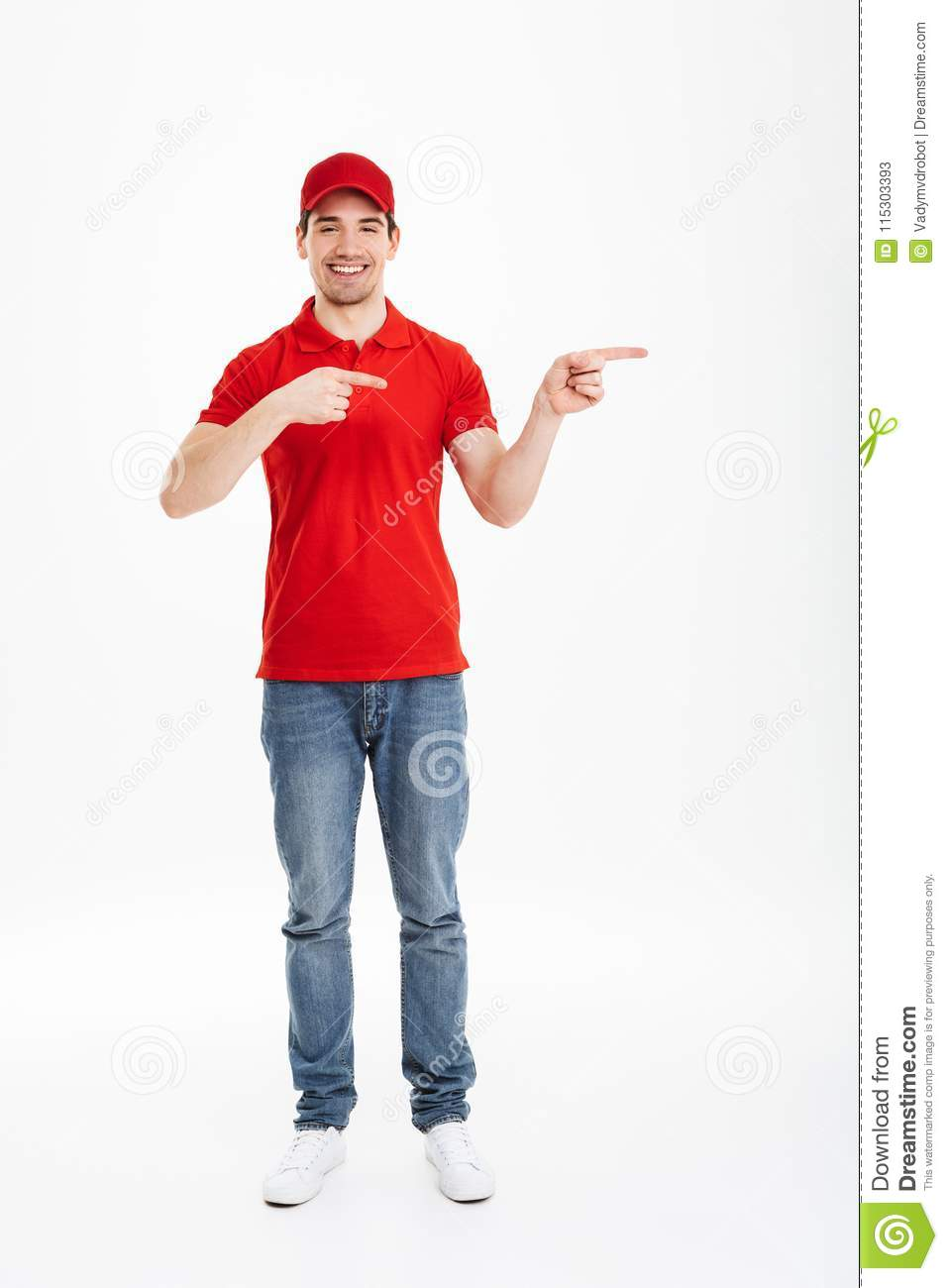 Full length photo of cheerful courier in red t-shirt and cap presenting copyspace text or product with pointing fingers aside and