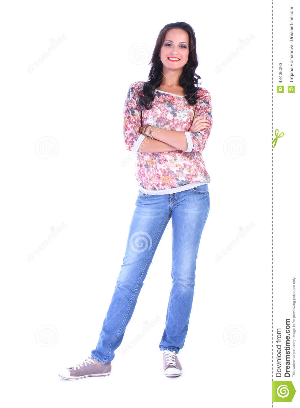 Full length picture of young woman in jeans standing