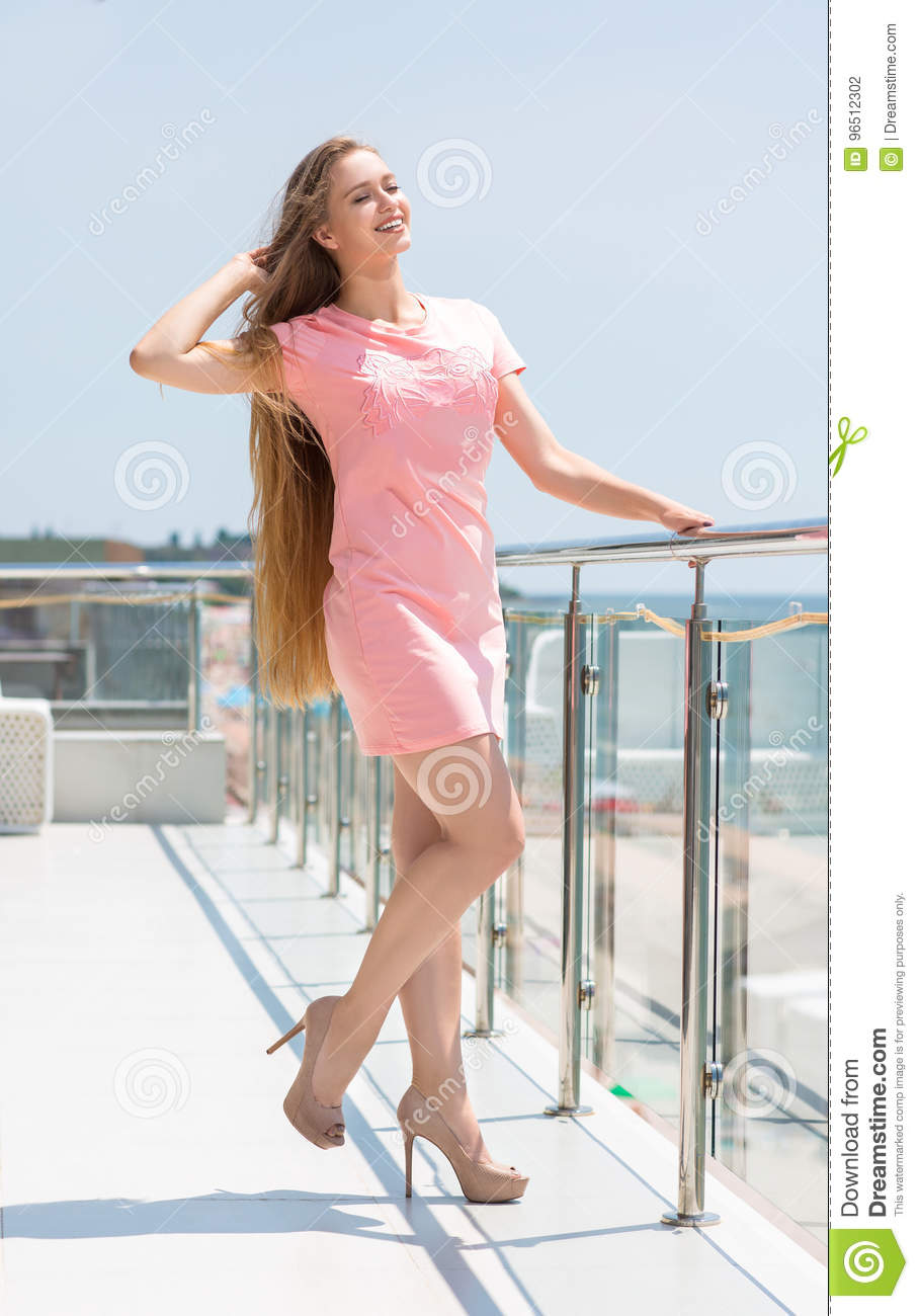 Full-length portrait of an attractive blond woman with long straight blonde hair in a pink dress. Fashion model with long hair.