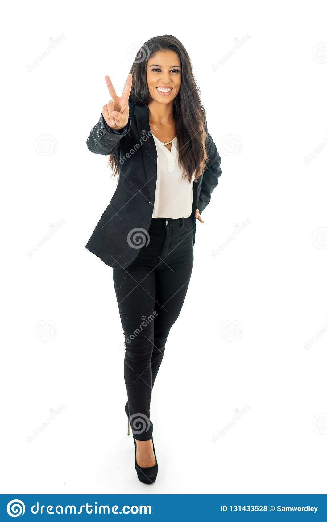 Full length portrait of a beautiful latin businesswoman smiling and making thumbs up sign standing isolated on a white background