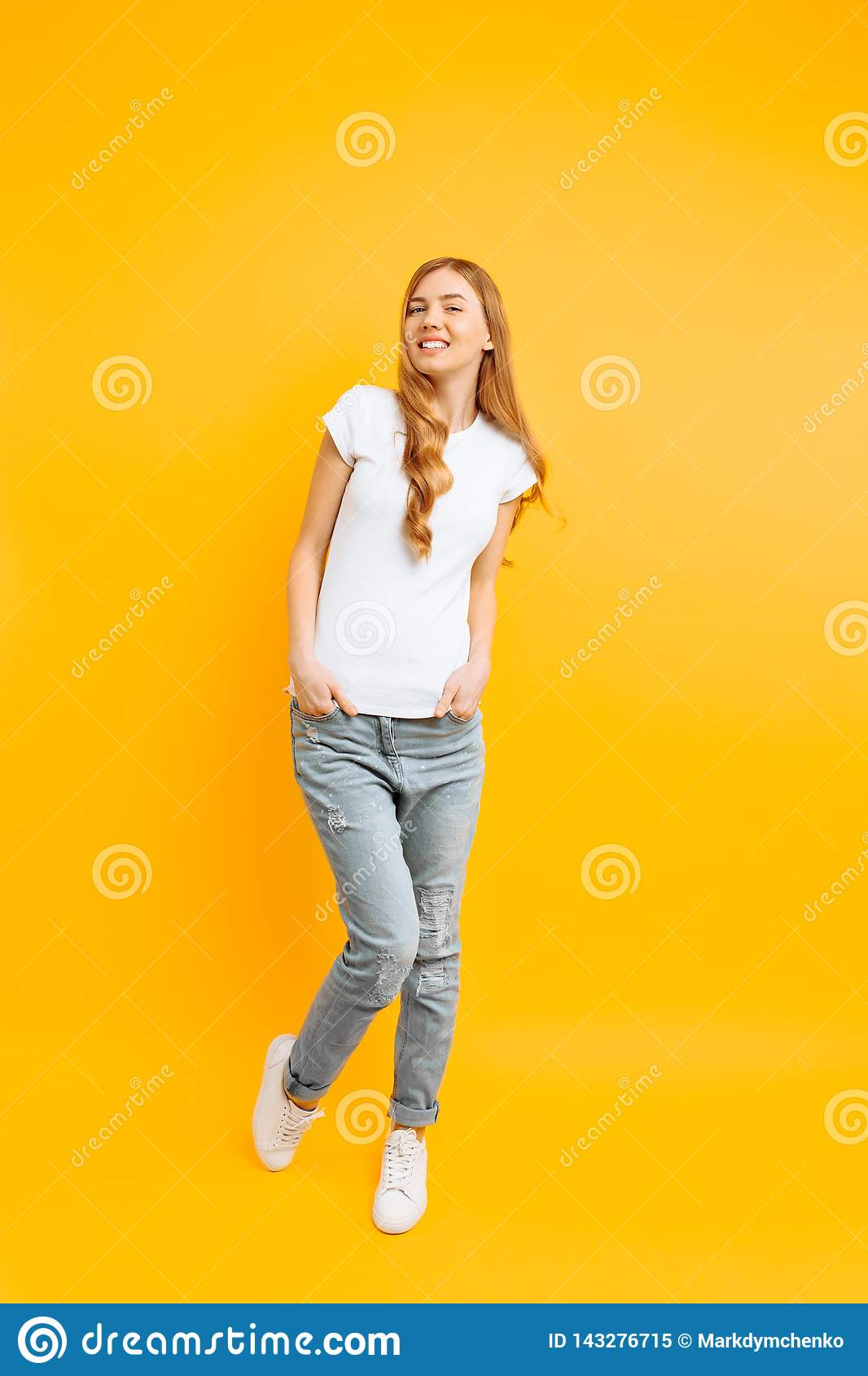 Full length portrait of a cheerful beautiful girl, posing on a yellow background