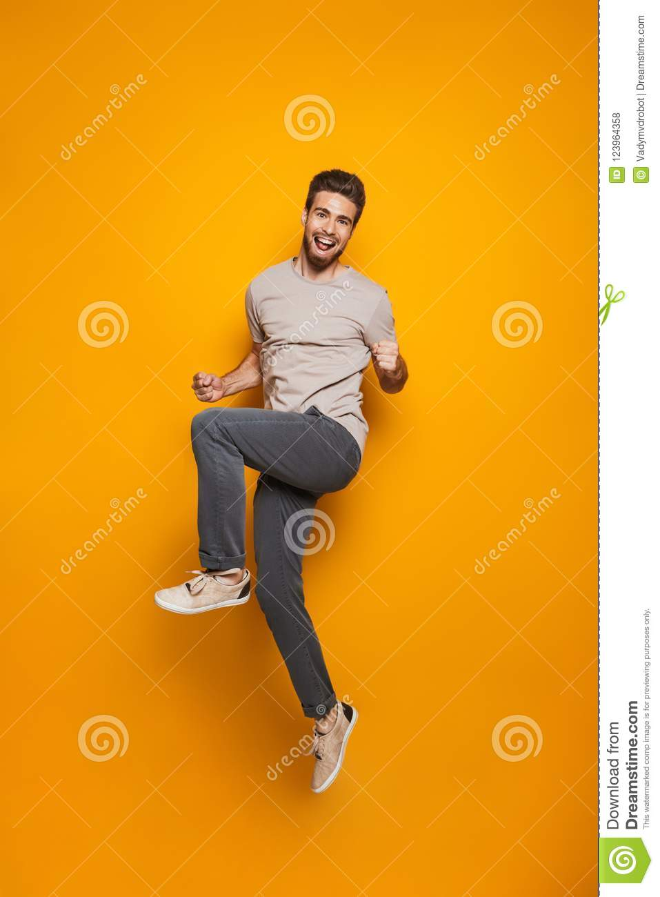 Full length portrait of a cheerful young man jumping