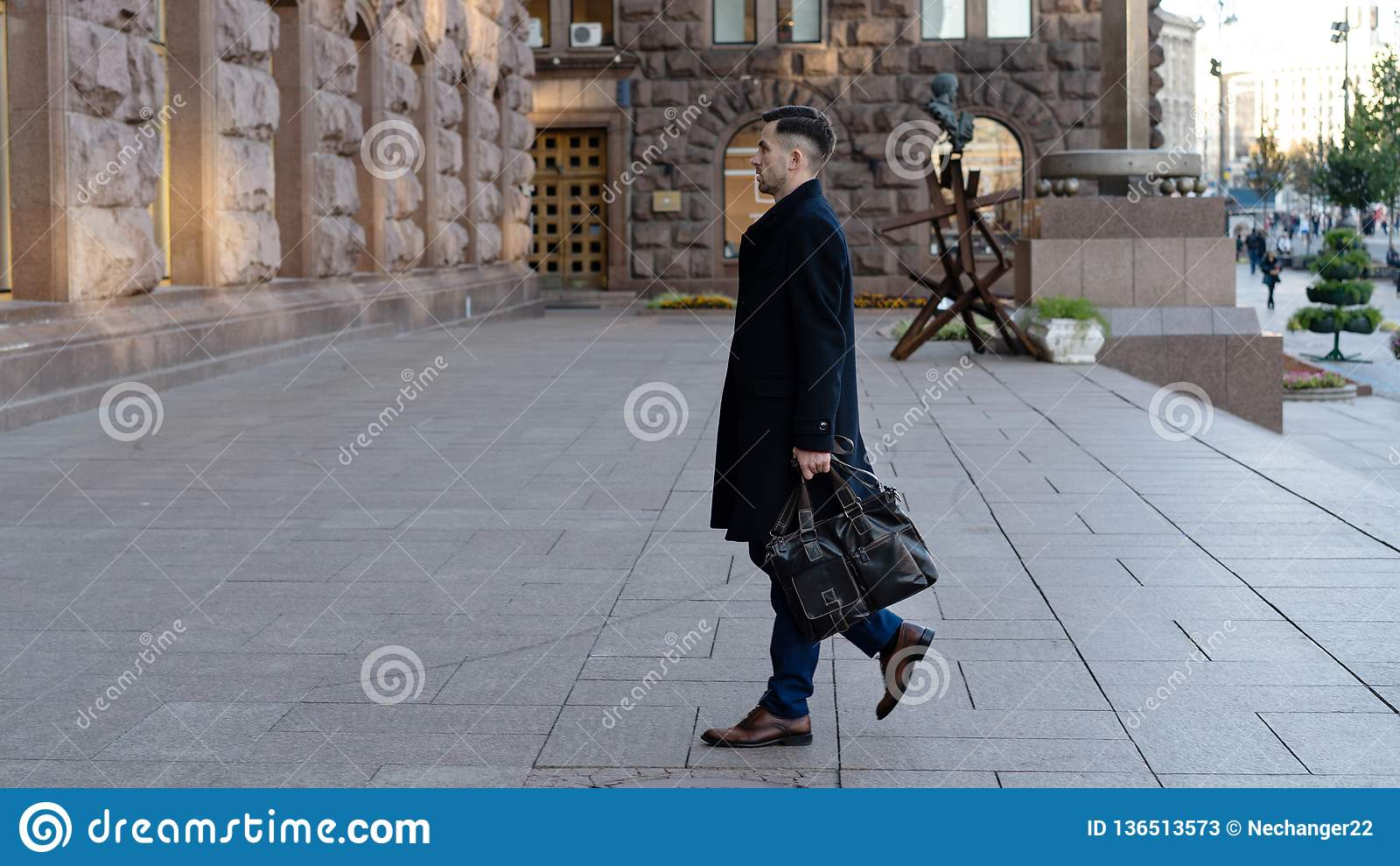 Full length portrait of a confident young businessman walking in the city with a bag