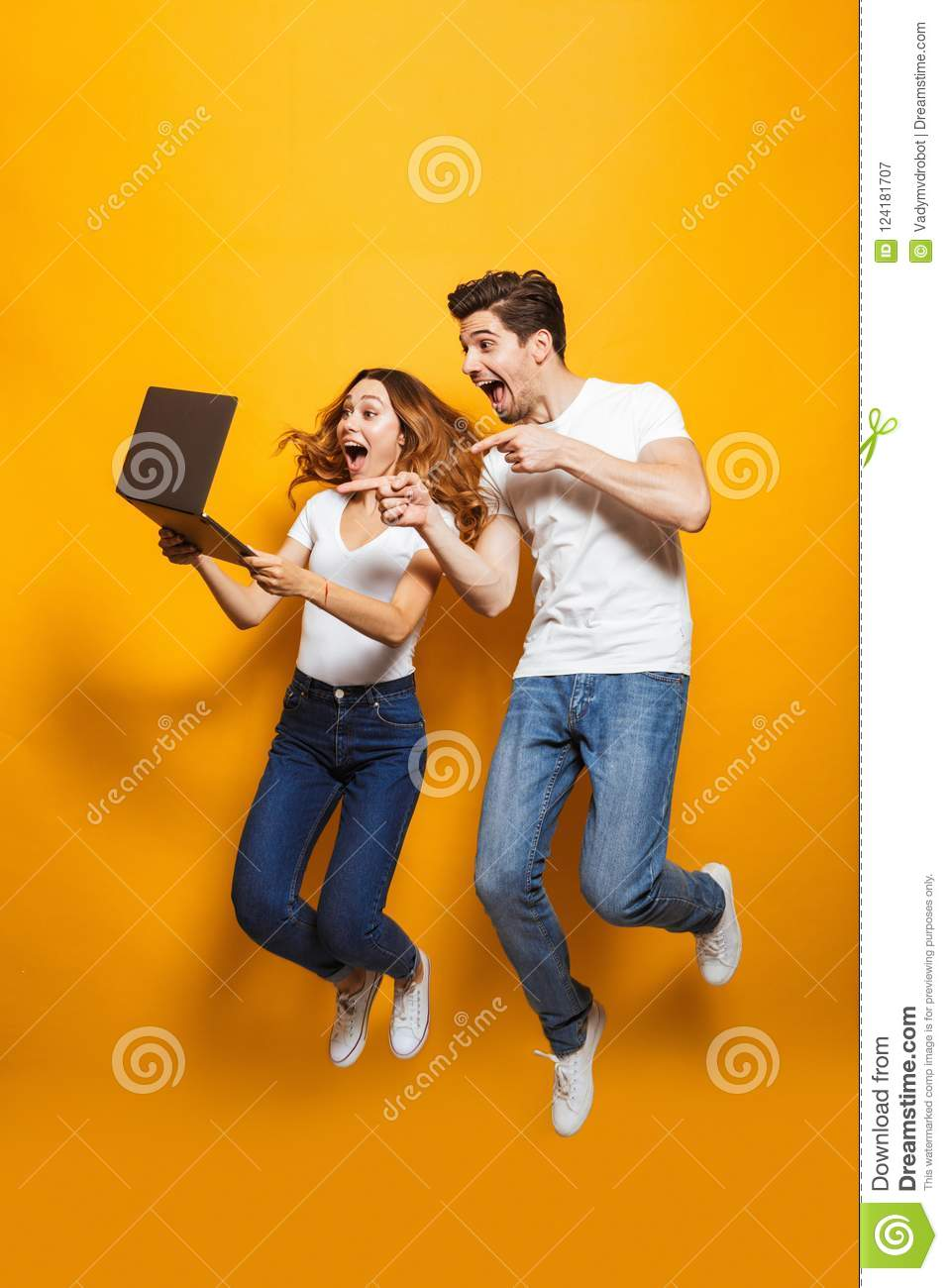 Full length portrait of excited man and woman jumping and using