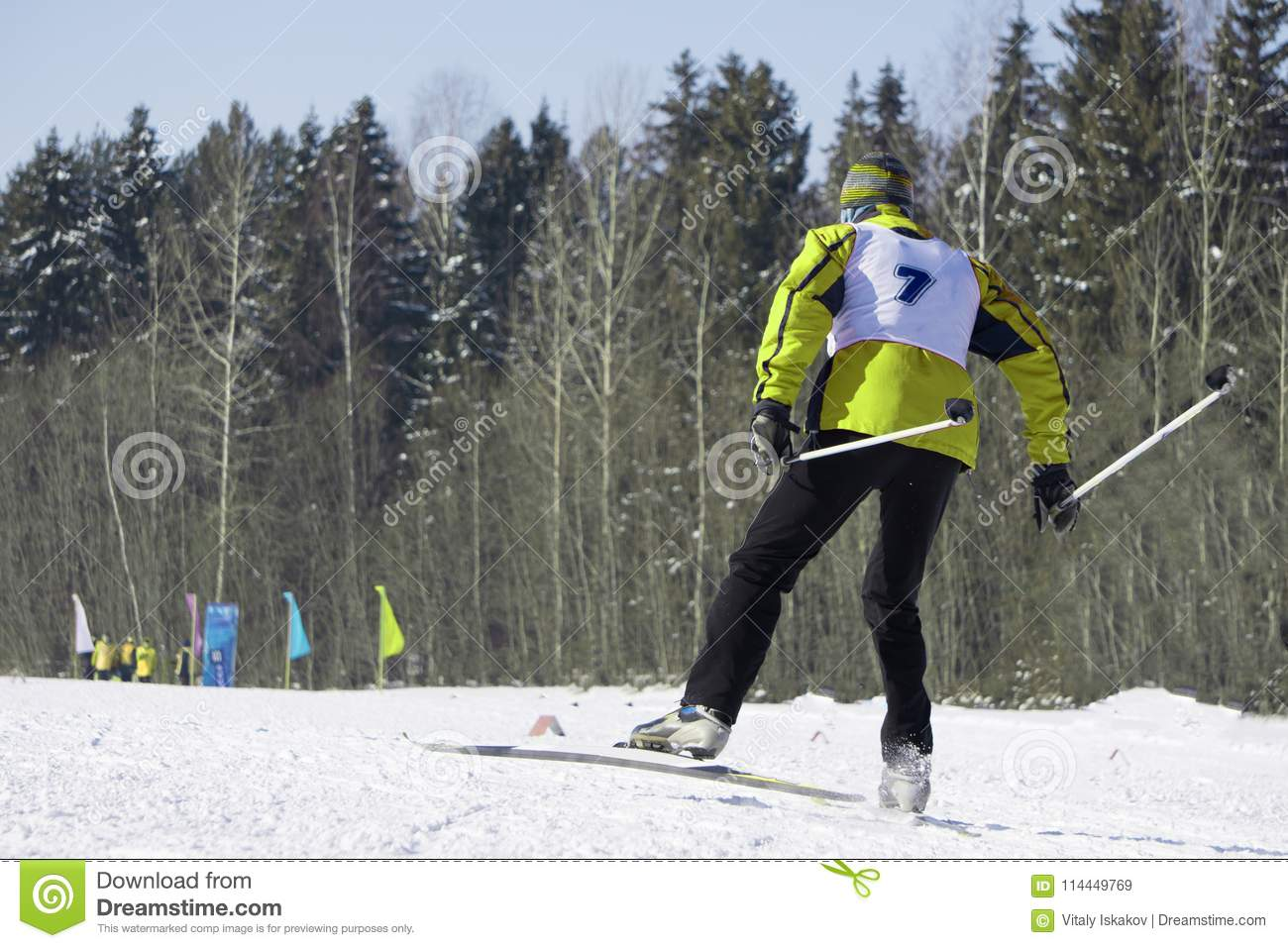 Full length portrait of a female skier standing with one leg raised on a ski slope on a Sunny day against a ski lift. Winter vacat
