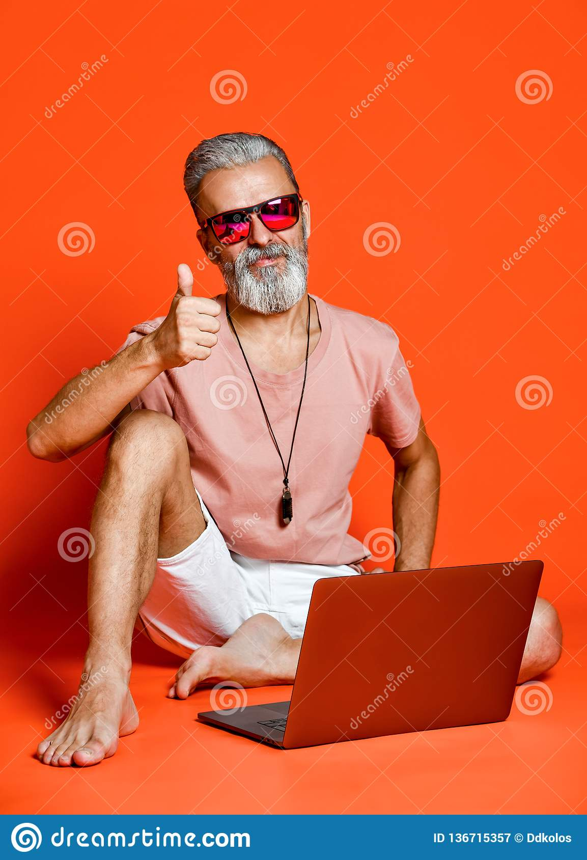 Full length portrait of a happy old man using laptop computer isolated over orange background