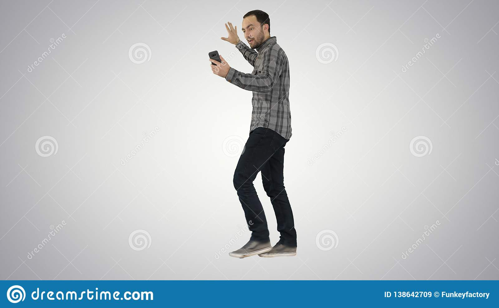 Handsome bearded man recording vlog blog with smartphone while walking on gradient background.