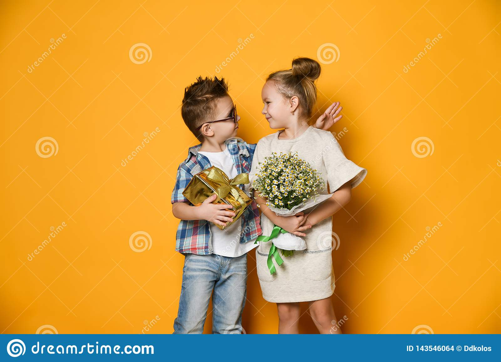 Full length portrait of a smiling man giving a present box to his girlfriend over gray wall