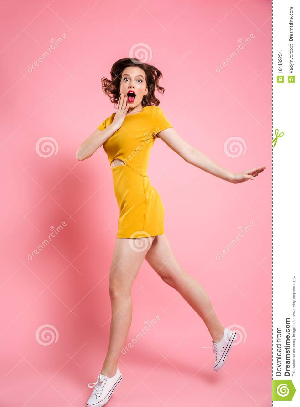 Full length portrait of surprised beautiful young woman in elegant yellow dress looking at camera while jumping over pink