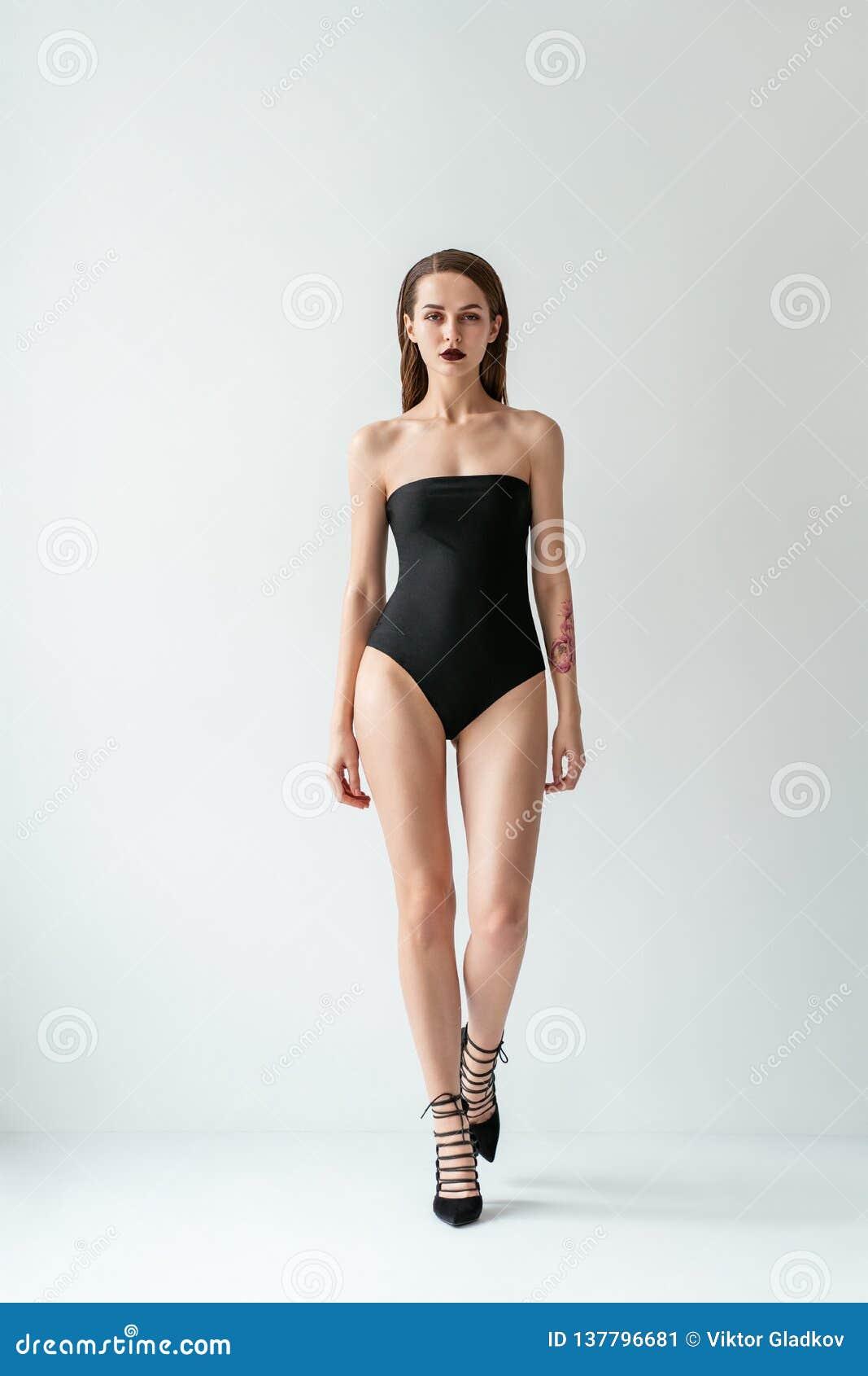 Full length portrait of walking beautiful girl in black swimsuit