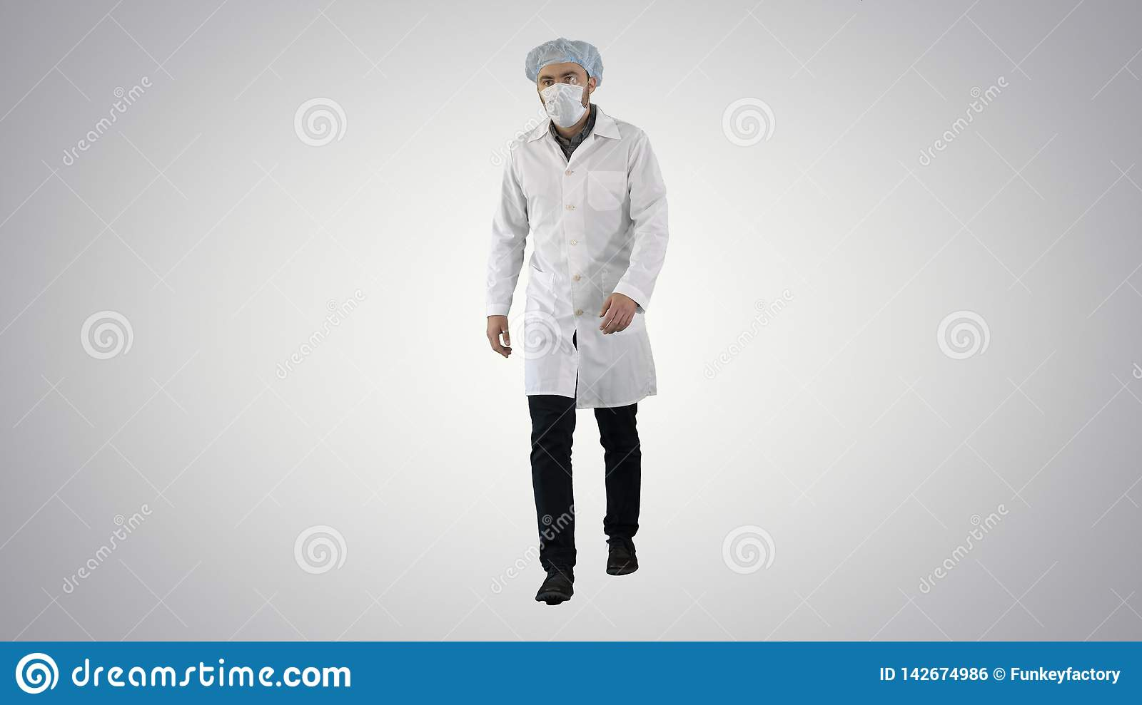 Walking young male doctor in a mask and a medical cap on gradient background.