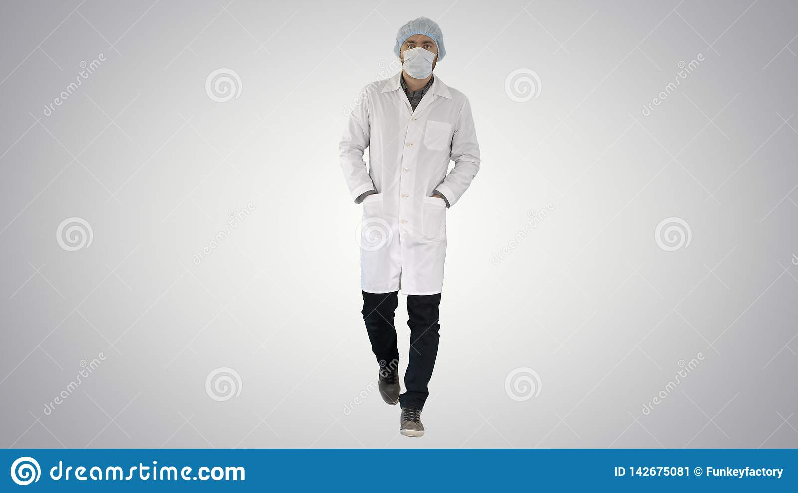 Walking young male doctor wearing surgical mask on gradient background.