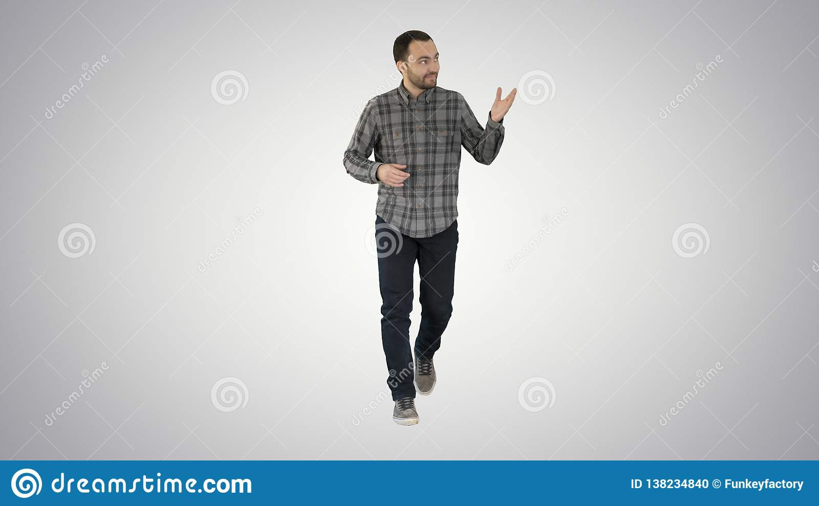 Young confident man in shirt and jeans walking towards camera and pointing to the sides on gradient background.