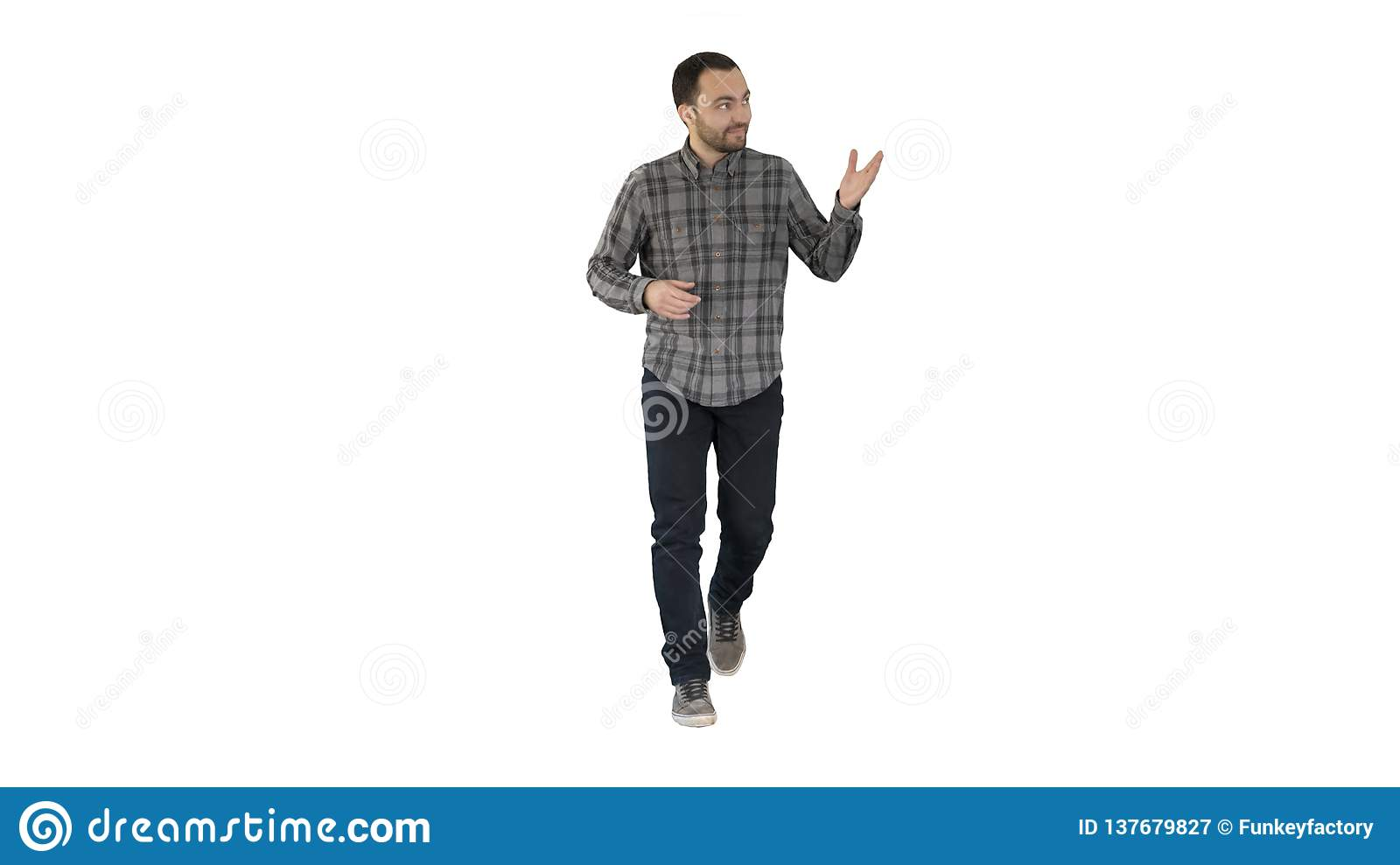 Young confident man in shirt and jeans walking towards camera and pointing to the sides on white background.