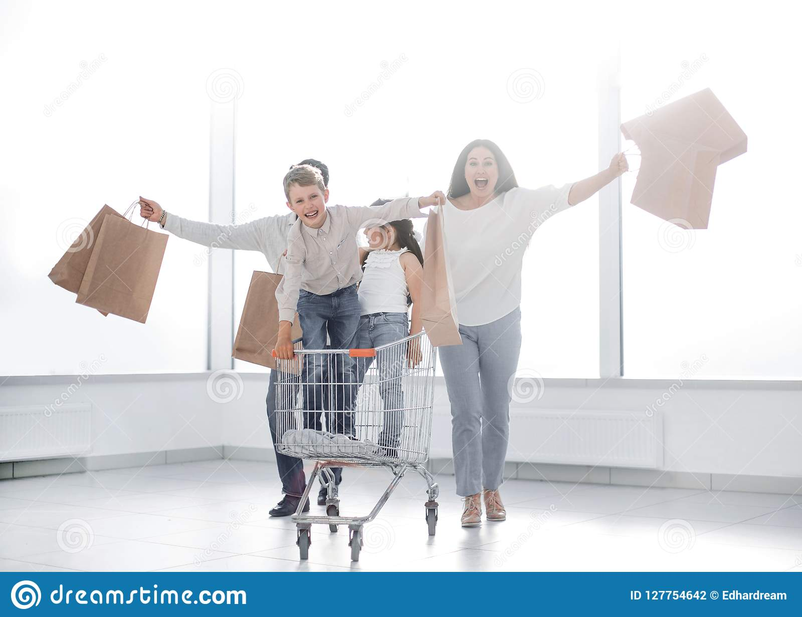 Full length portrait of a young family standing with shopping cart