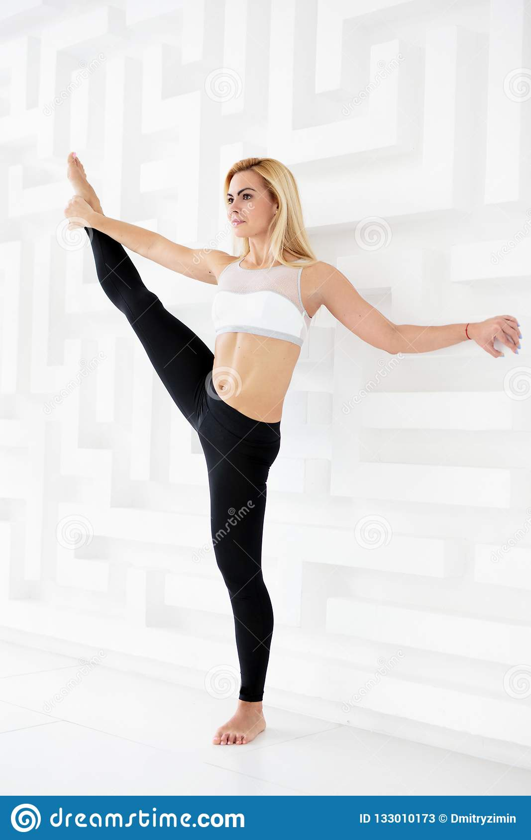 Full Length Portrait Of Young Woman Doing A Yoga Pose Standing