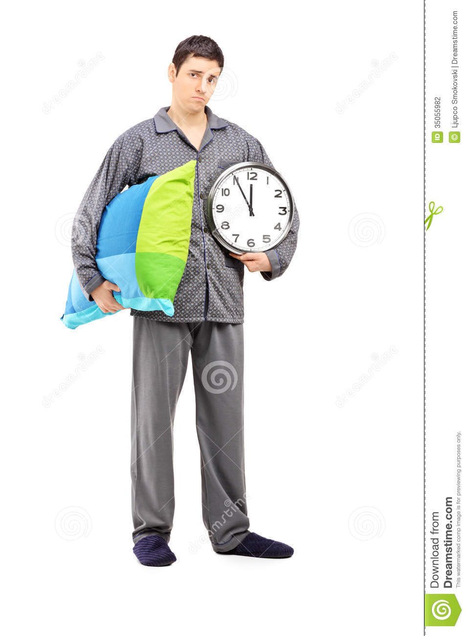 Full length portrait of young sleepy guy holding a wall clock an