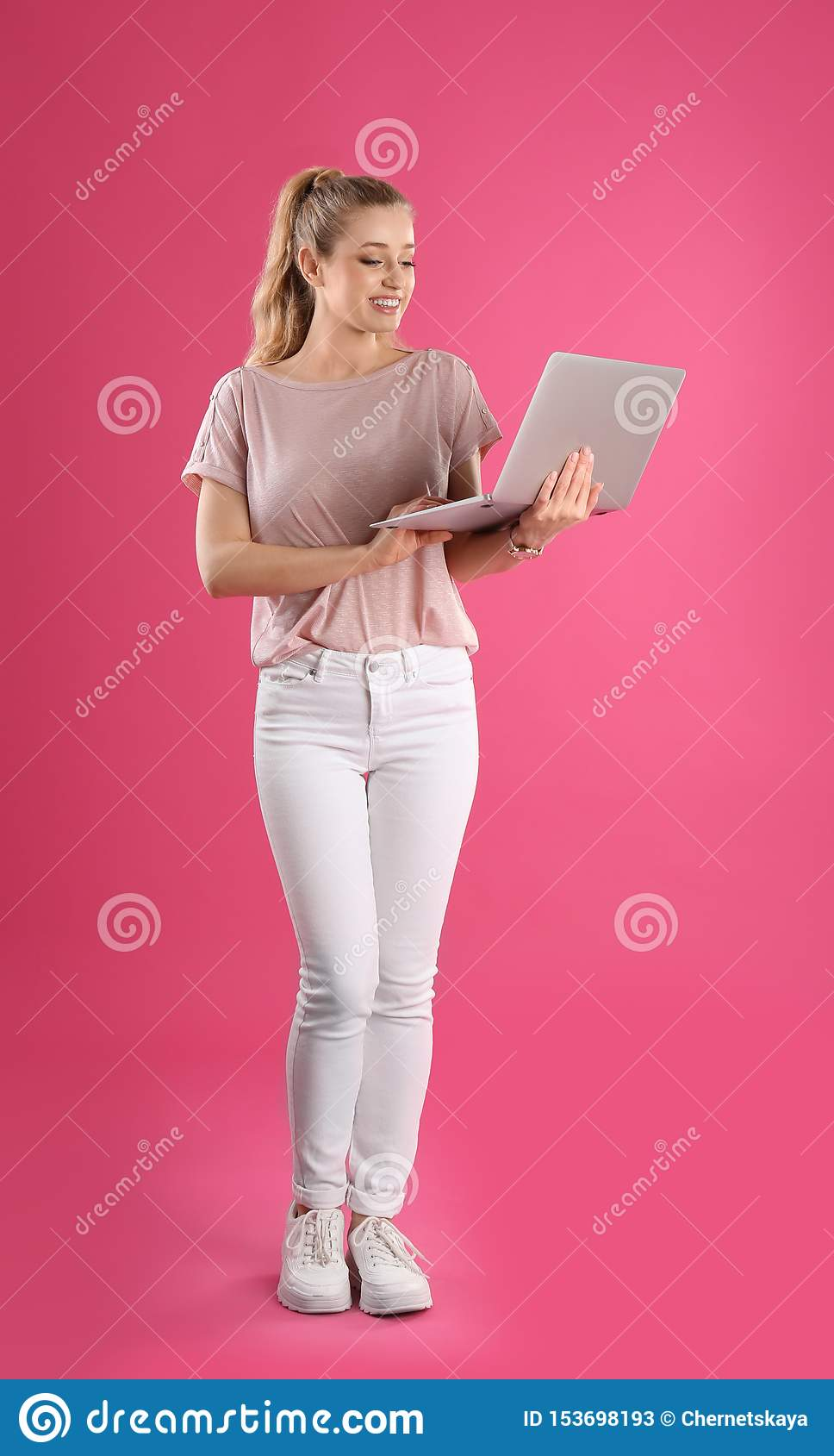 Full length portrait of young woman with laptop