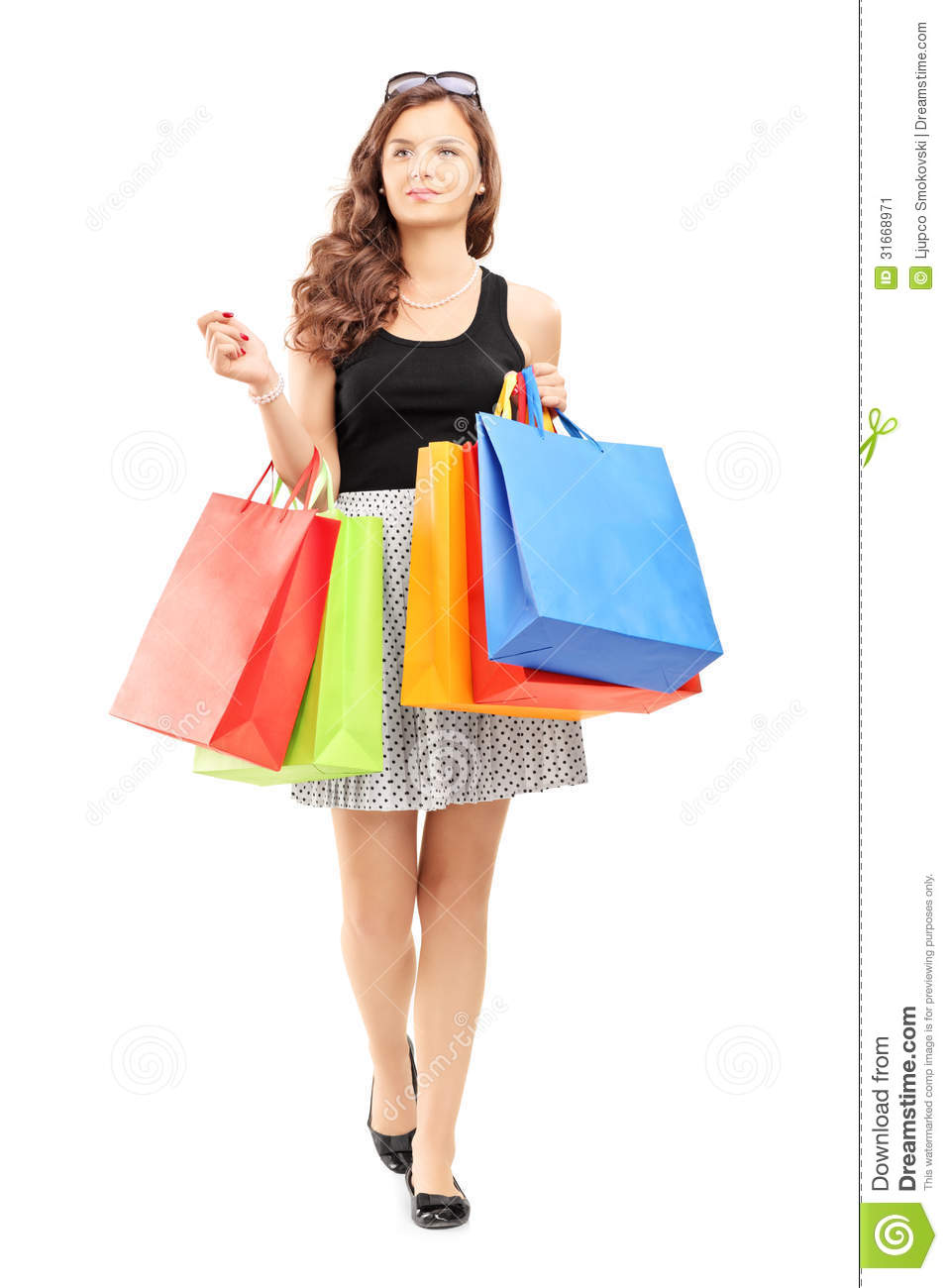 Woman posing with shopping bags isolated on white background full - Full Length Portrait Of A Young Woman Walking With Shopping Bags