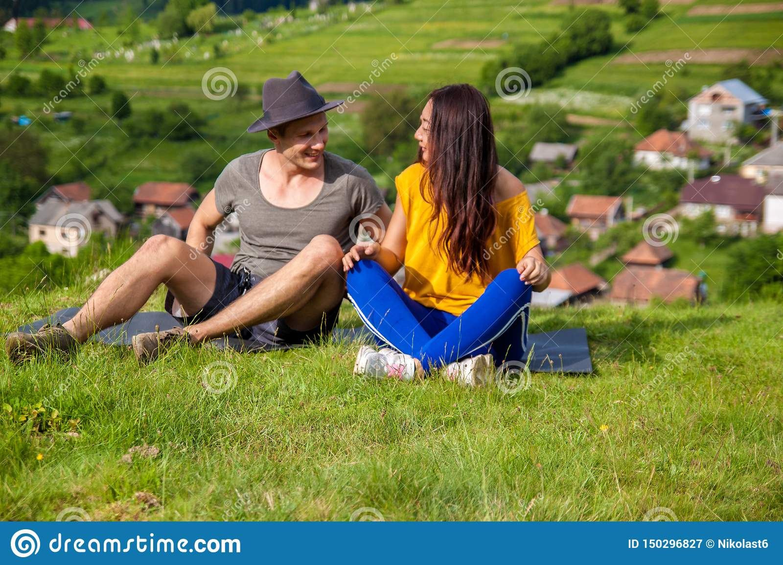 Full length of pretty girl and handsome man joyfully bounding to each other on green grass.