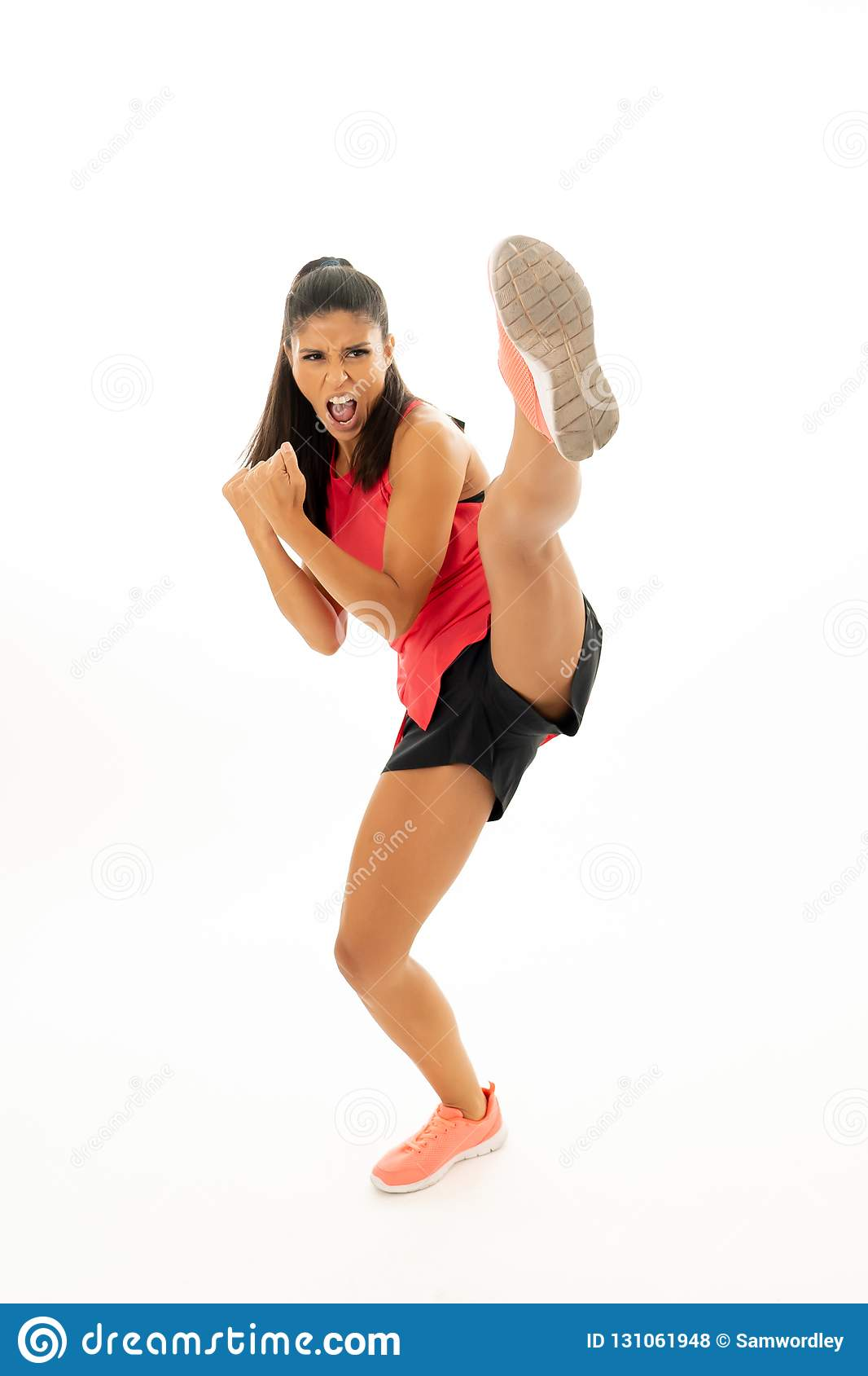 Full length shot of fit woman athlete performing a high kick martial Karate style