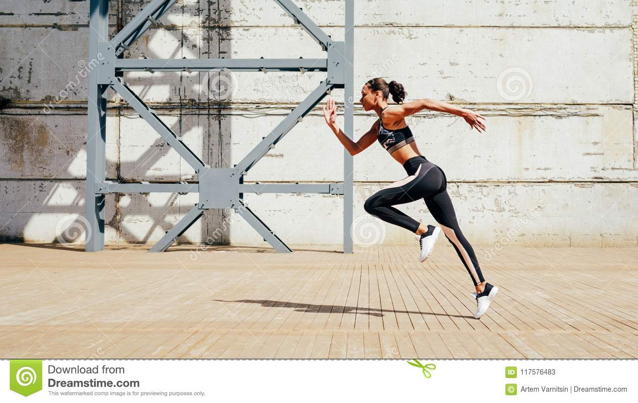 Full length shot of young female athlete sprinting in city.