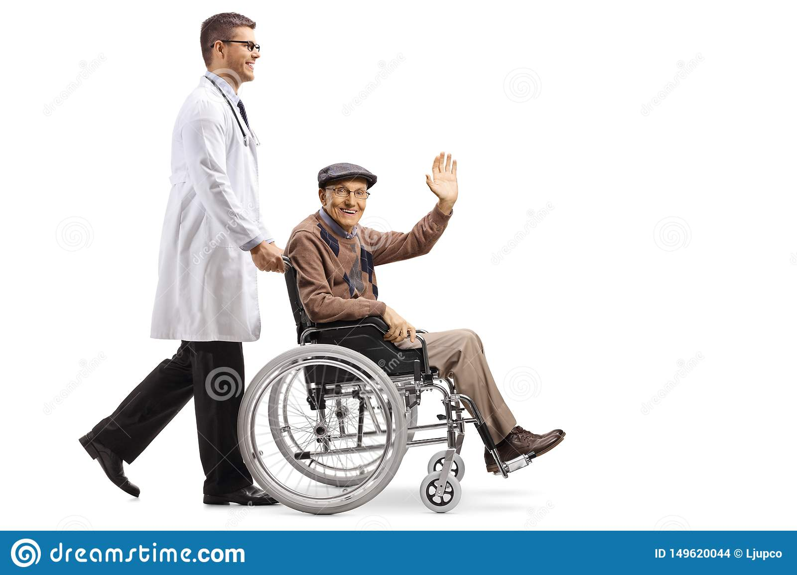 Young male doctor pushing a senior man sitting in a wheelchair and waving