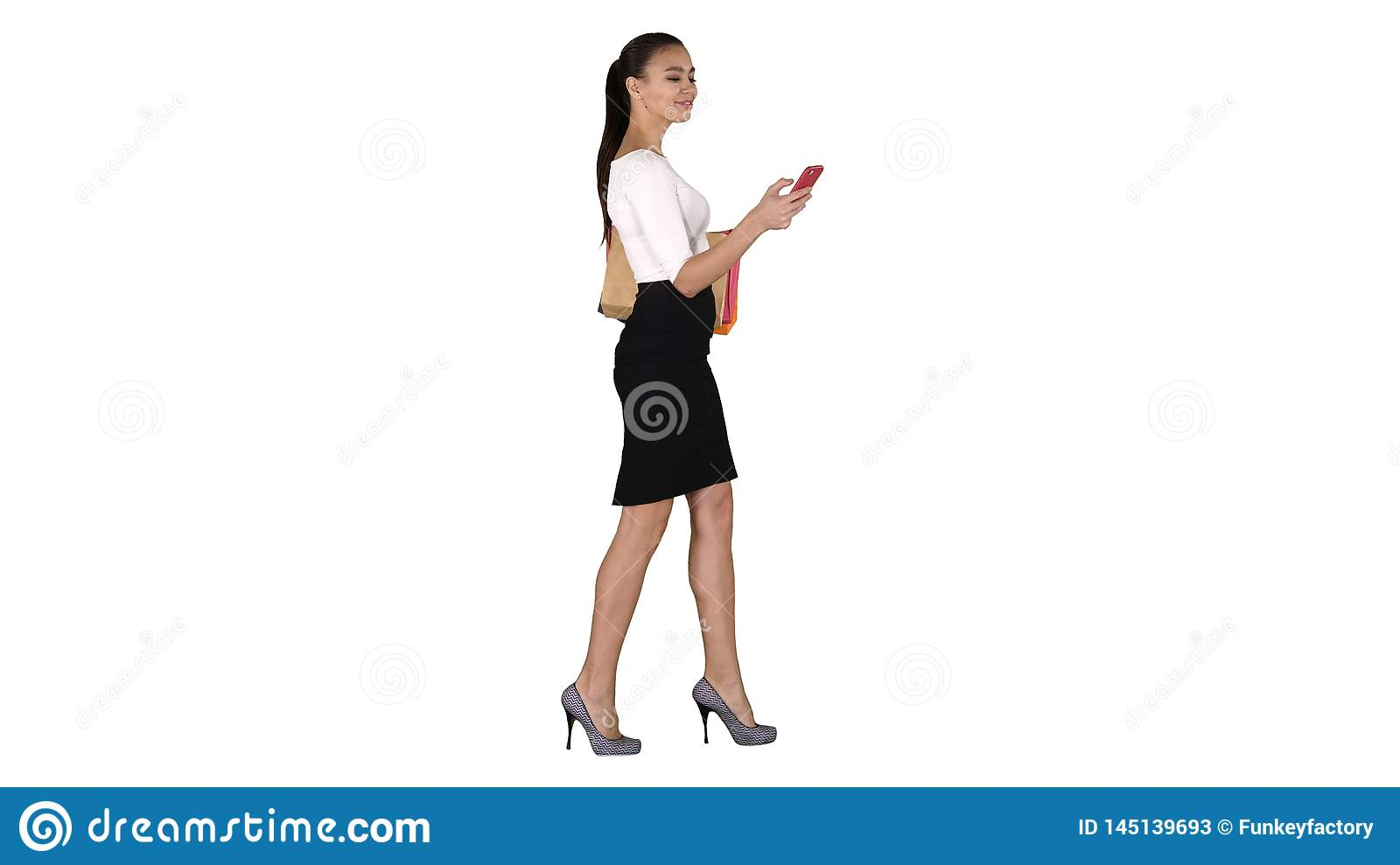 Young woman walking with shopping bags talking on mobile phone on white background.