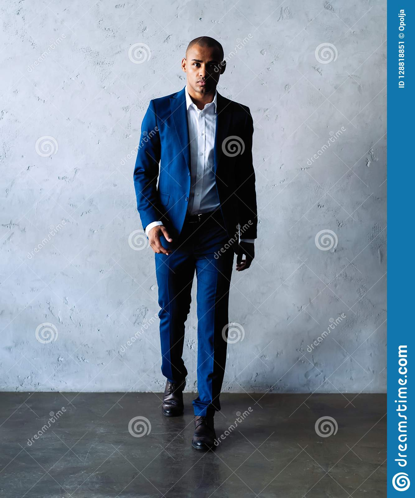 7b6066babf Full length smiling business man in black suit looking at camera and  standing isolated on gray background
