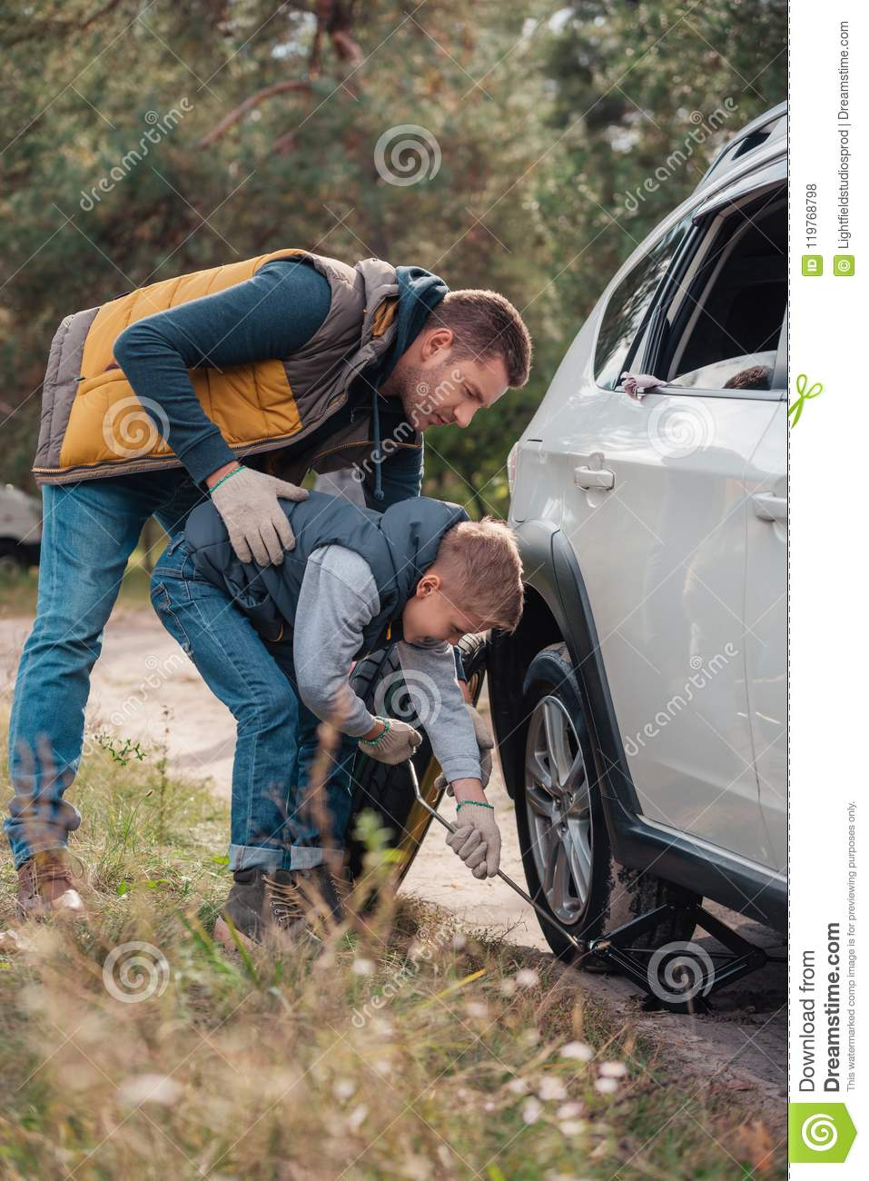 full length view of father and son changing car wheel together