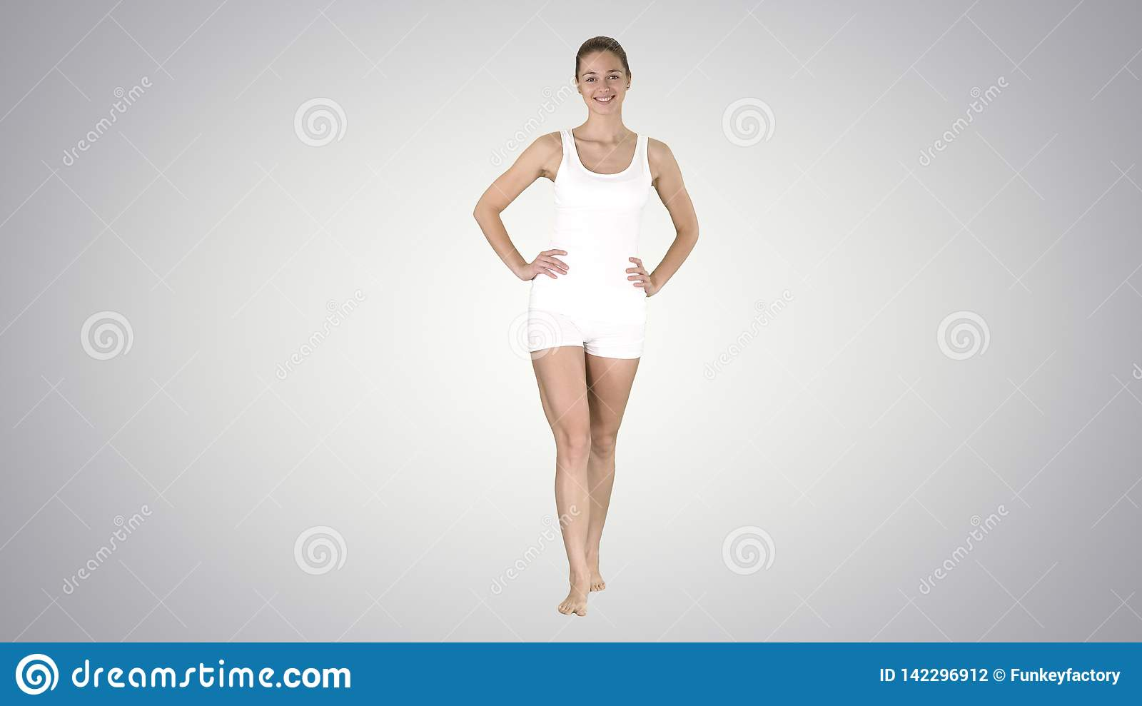 Fit and sporty girl in gradient underwear walking barefoot with hands on her hips on gradient background.