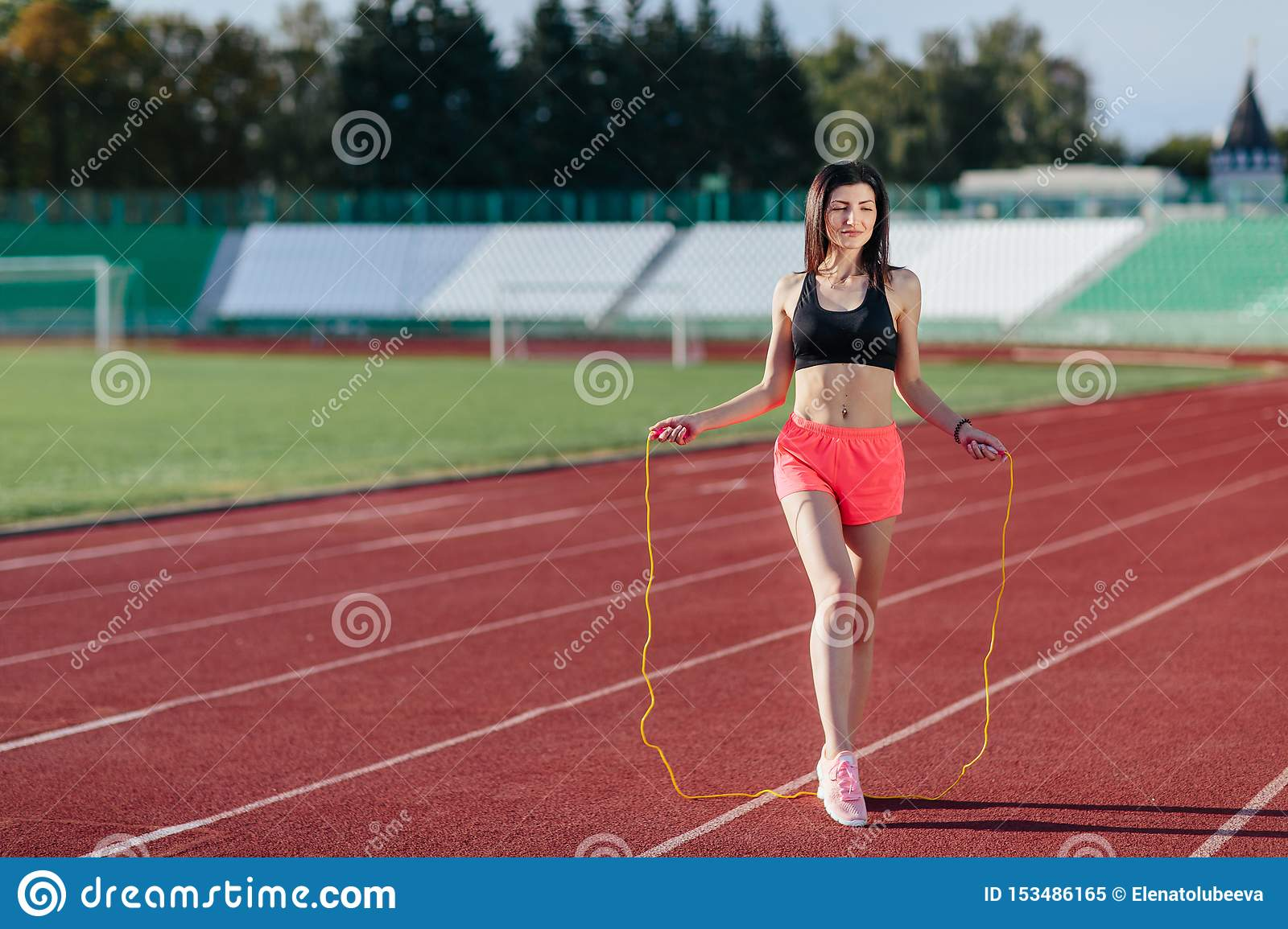 Full length view of young sport brunette woman in pink shorts and black top exercising with skipping rope on stadium